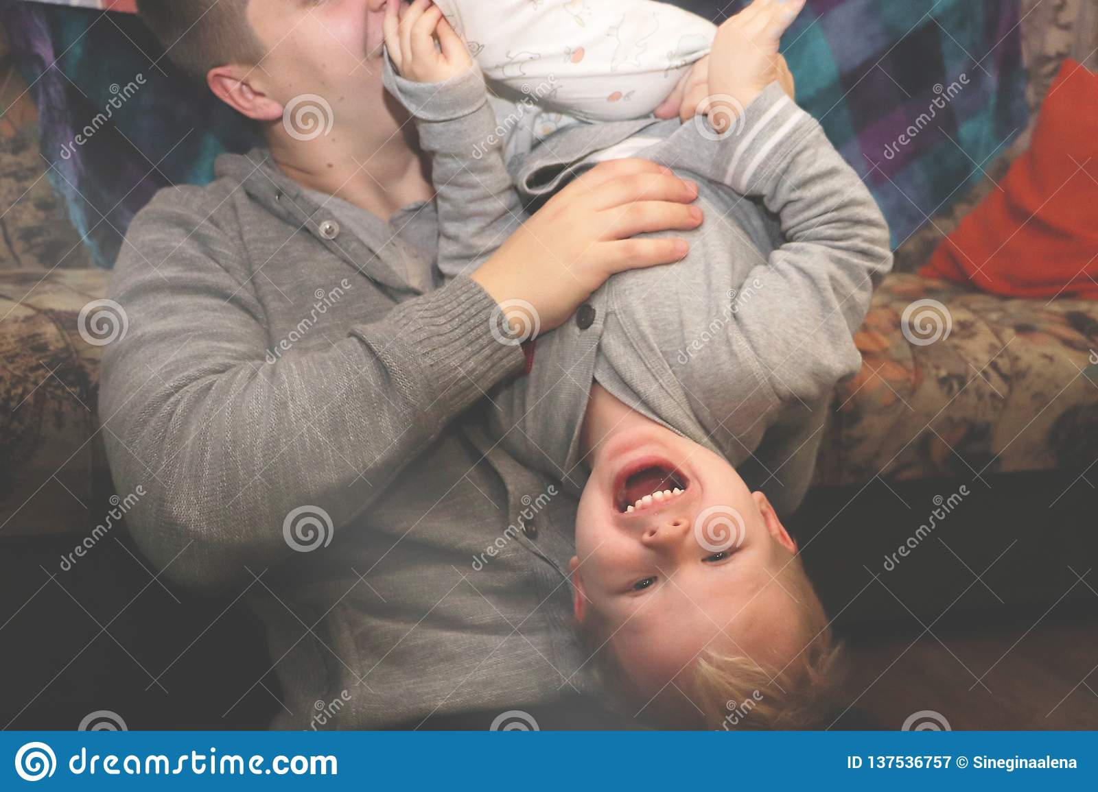 Dad and son play, indulge. The father turned his son upside down, the child laughs