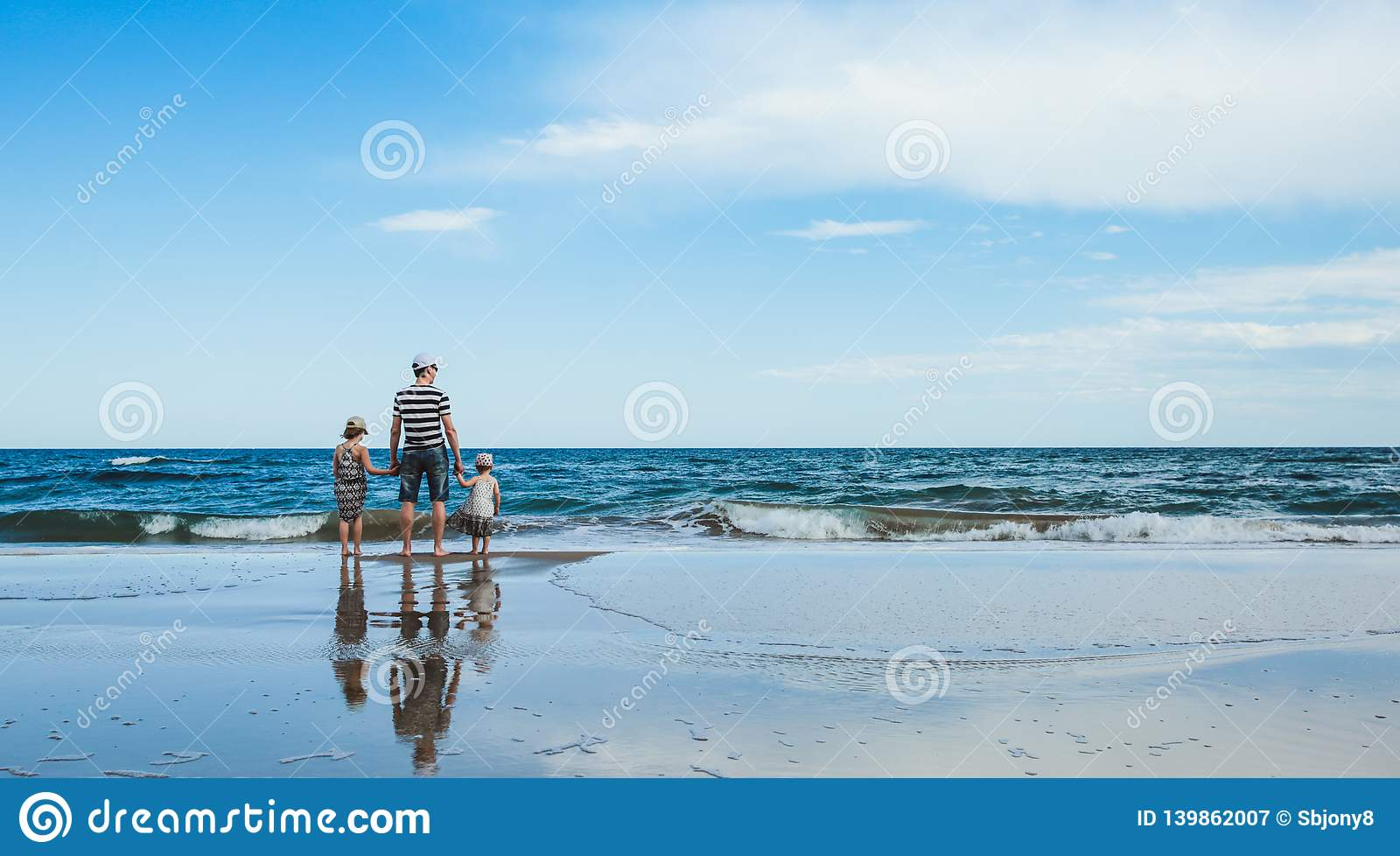 father and two daughters standing at the beach