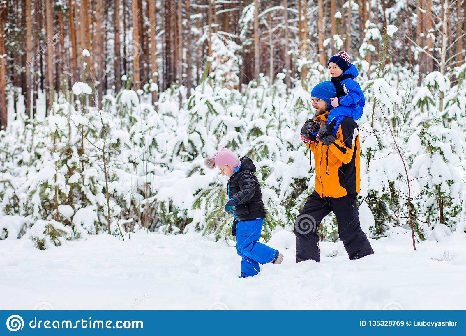 Father walks with his young children in the woods in winter
