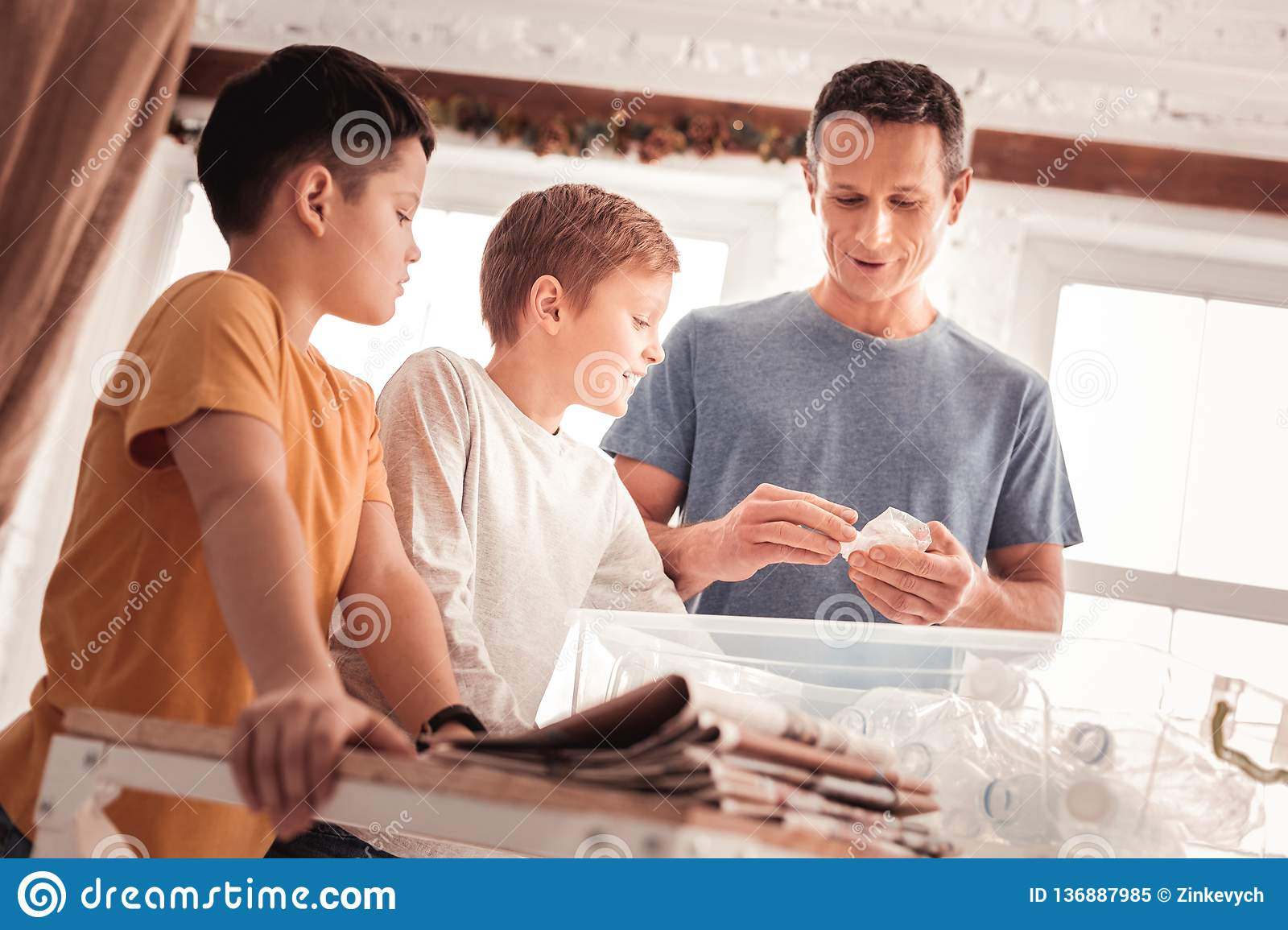 Father wearing blue shirt telling his sons about waste sorting