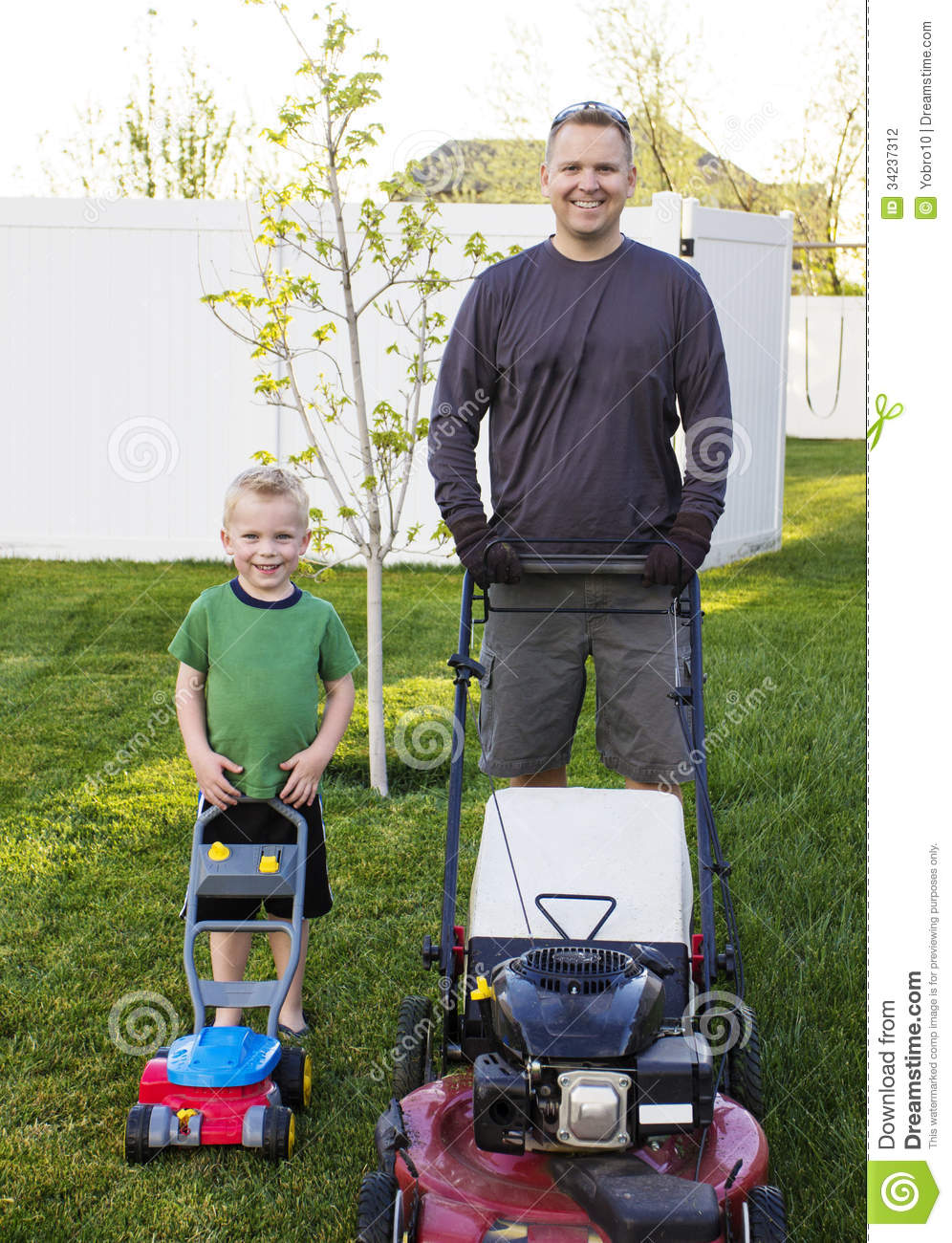 Father And Young Son Mowing The Lawn Together Stock Photo