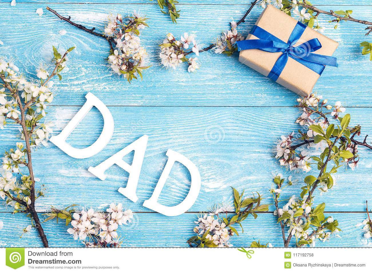 fathers day message with apple blossoms and gift box on blue woo