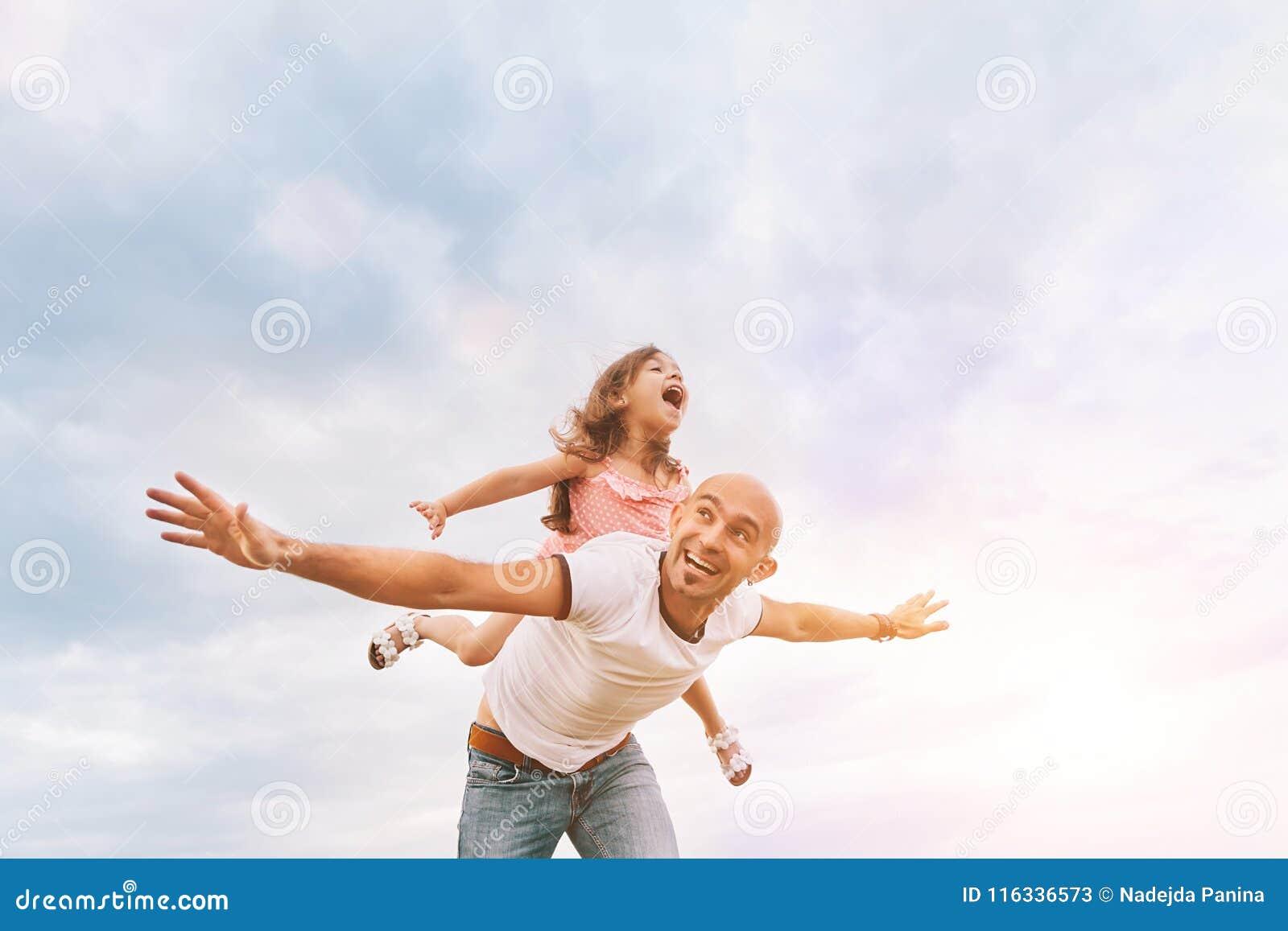 Fathrer e hija linda que juegan como el aeroplano
