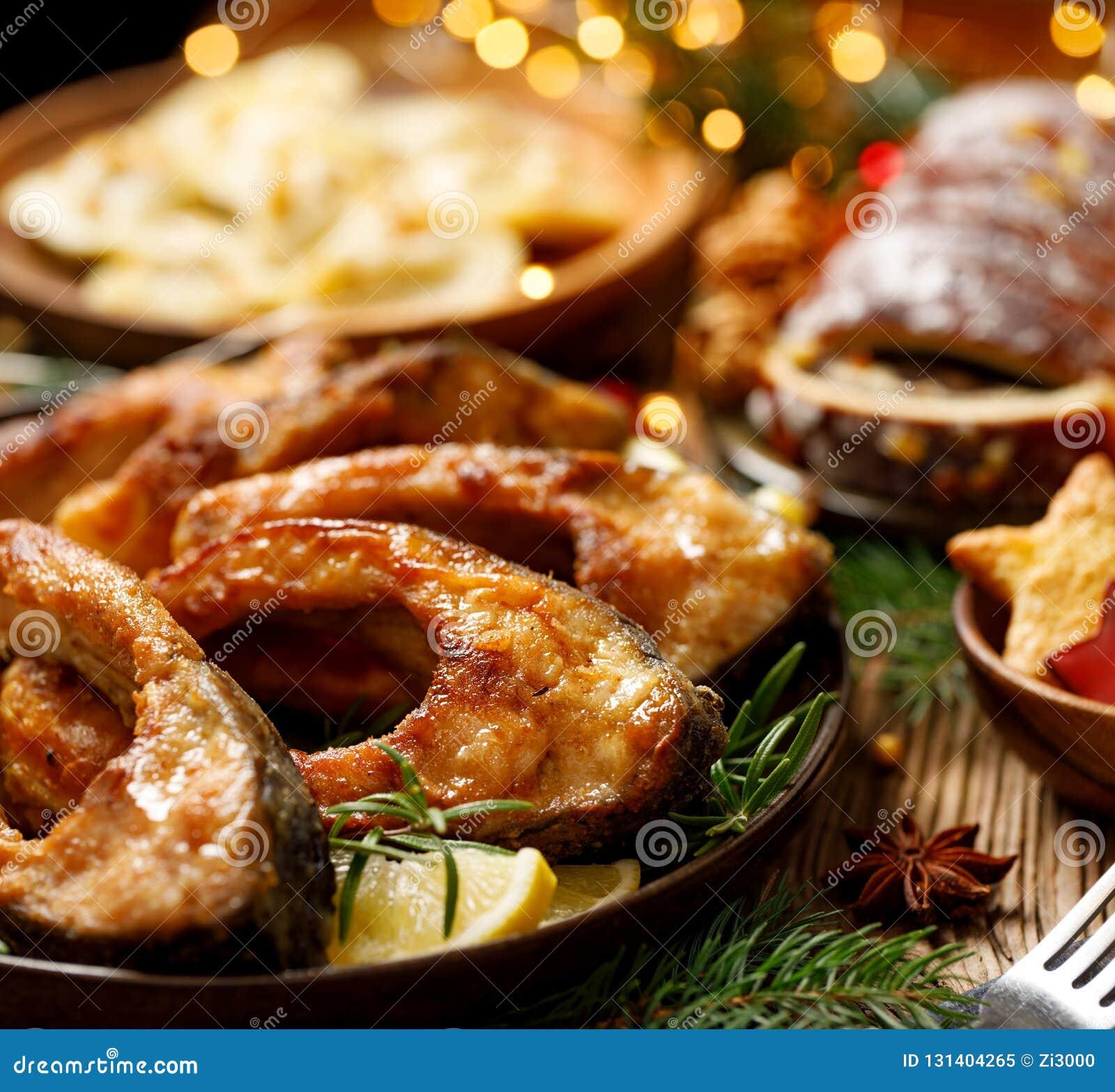 Fatias de peixes fritadas em uma placa cerâmica, fim da carpa acima Prato tradicional da Noite de Natal