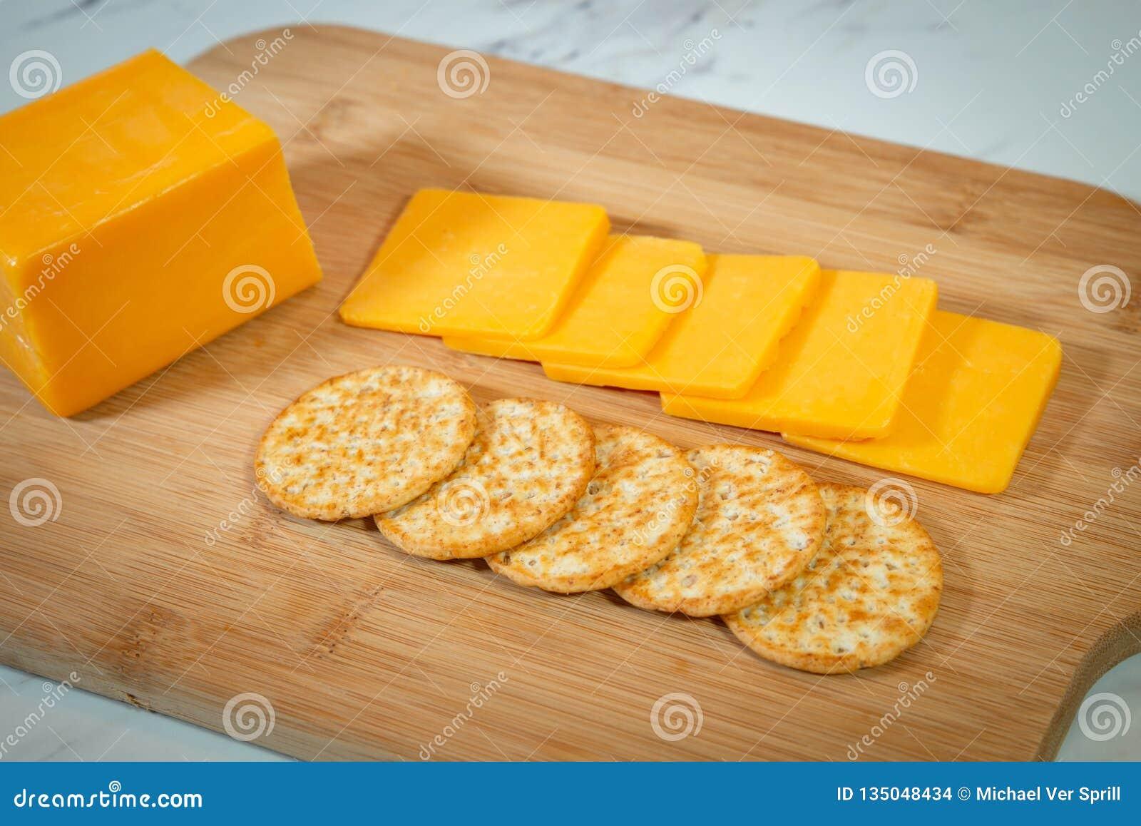 Fatias de queijo cheddar e de biscoitos em uma placa de corte