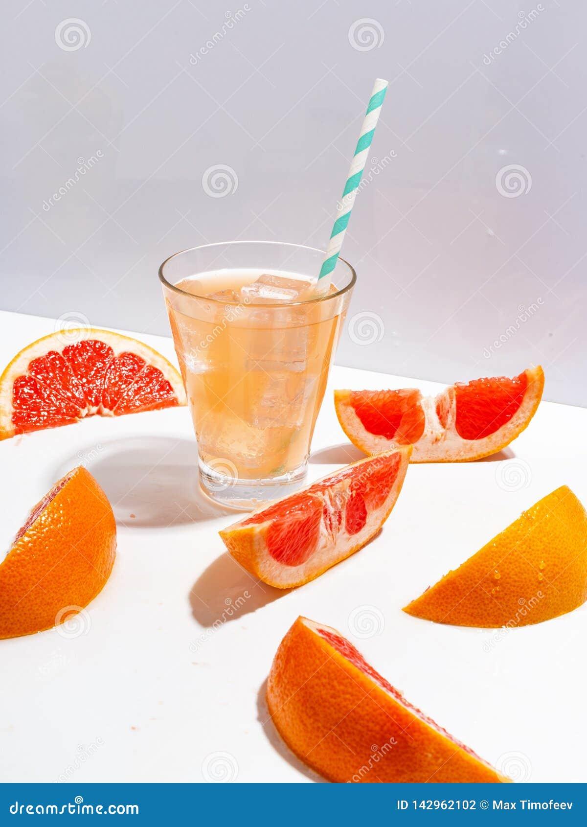 Fatias de toranja suculenta e de um vidro da limonada fresca com gelo em um fundo branco