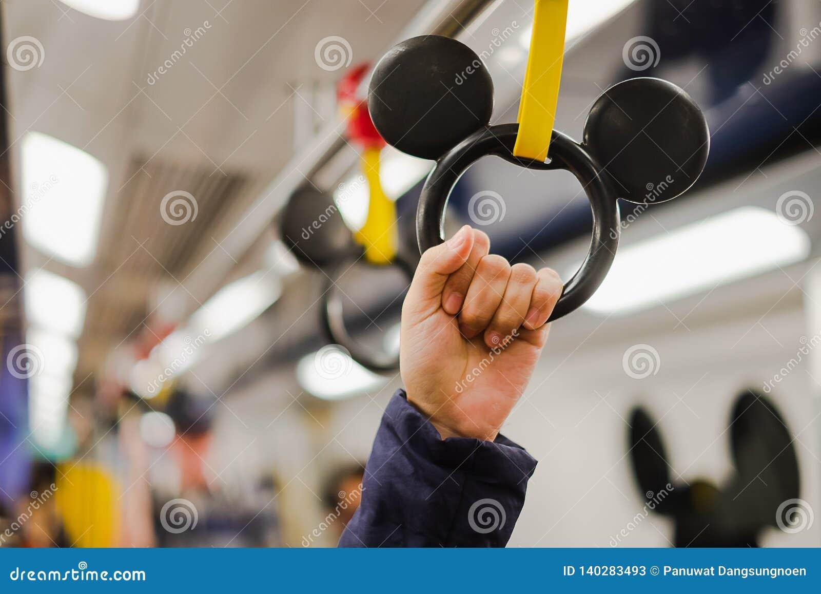 Fattande för kvinnainnehavhand i den Disney linjen MTR-insida från den soliga fjärden till den Hong Kong Disneyland semesterorten