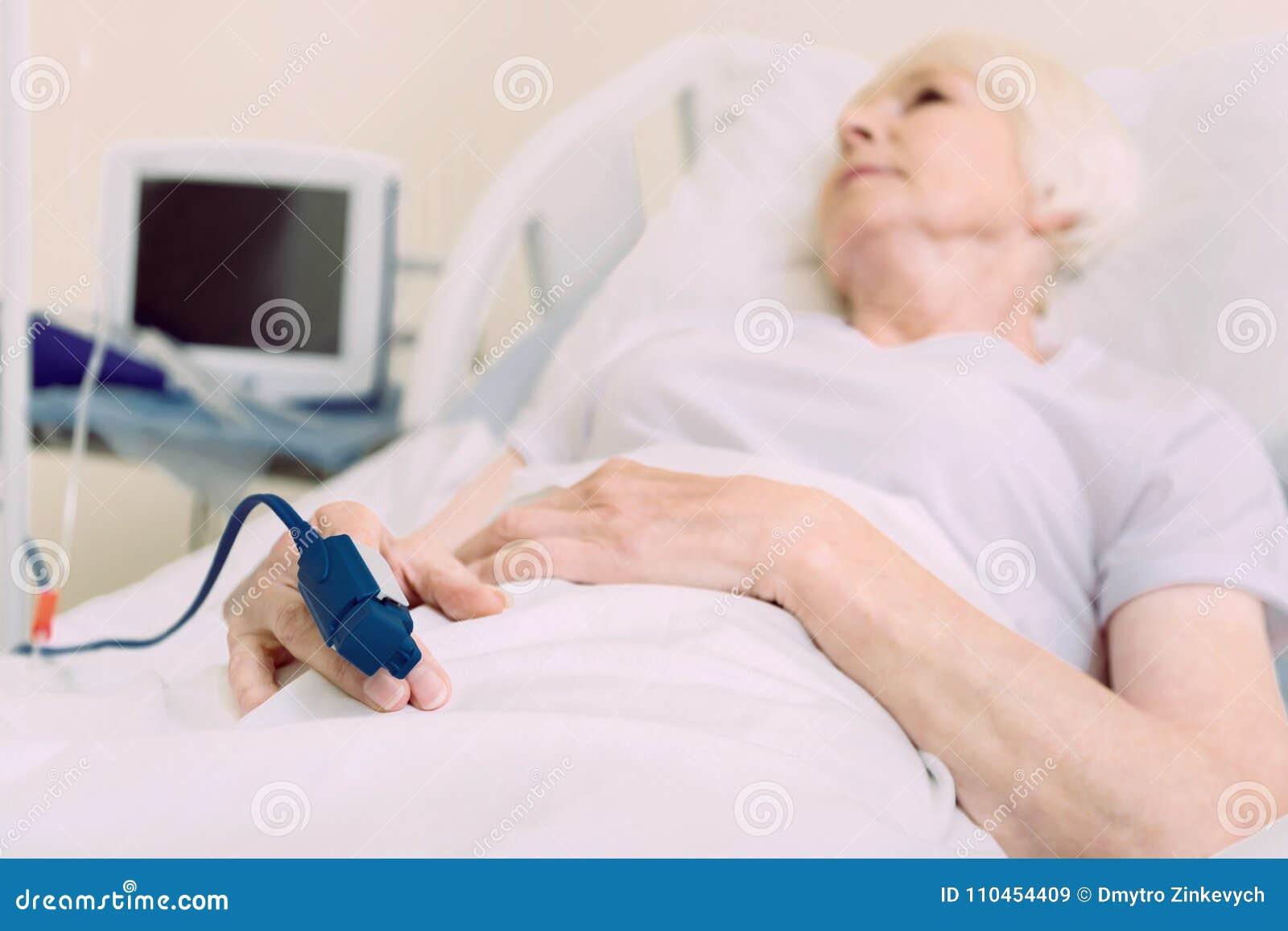 Fattig hög dam som ligger i sjukhussäng med pulsoximeteren