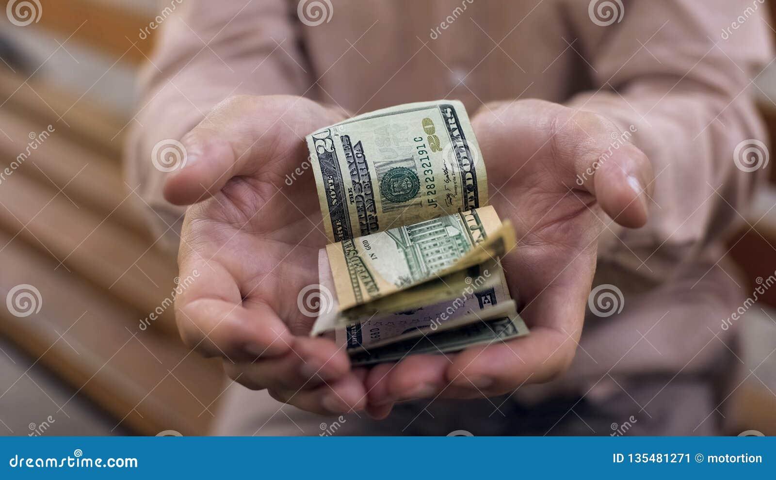 Fattig manlig pensionär som visar få dollarräkningar i händer, ekonomisk kris, behov