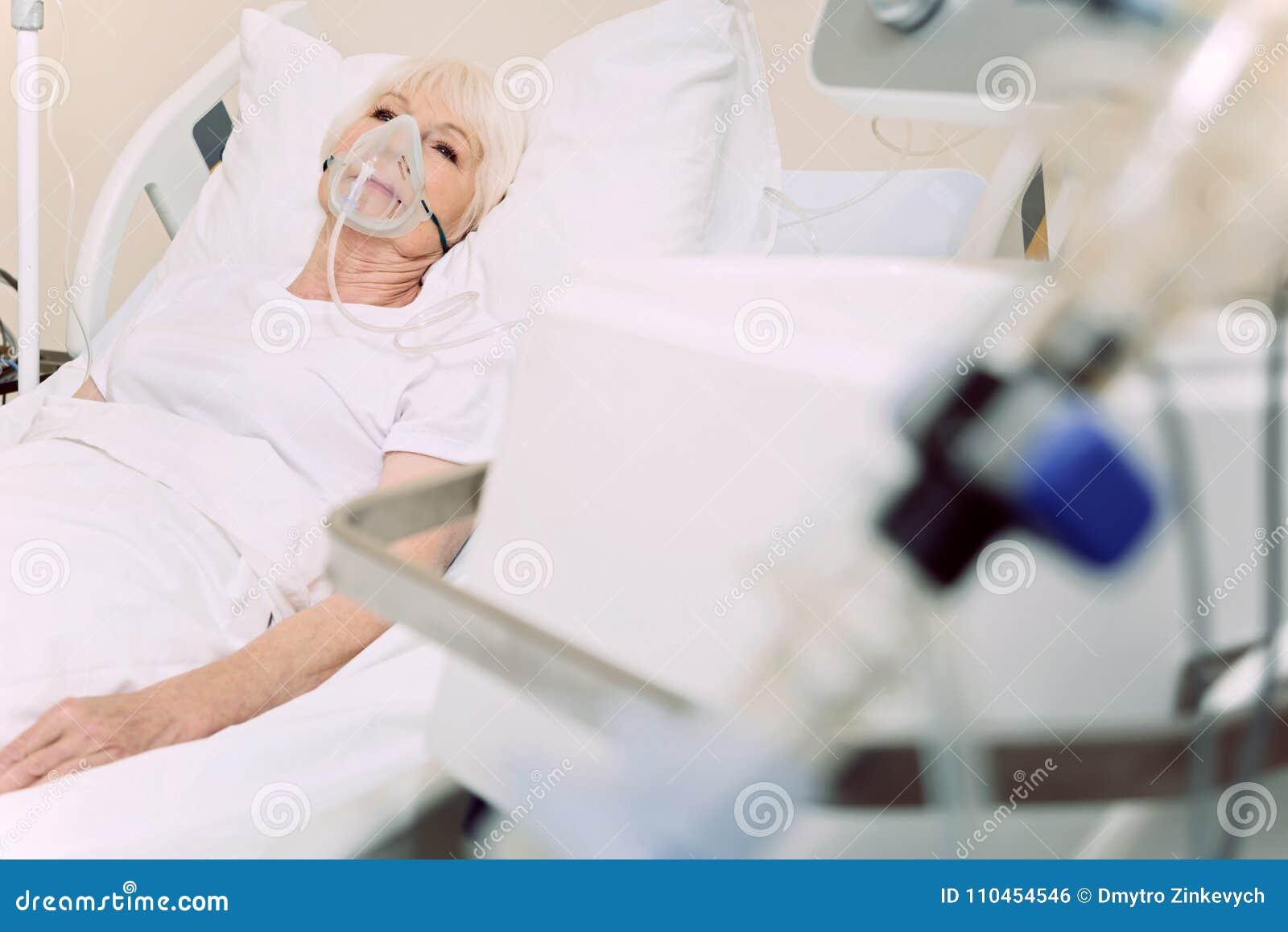 Fattig pensionerad kvinna med syremaskeringen på sjukhuset