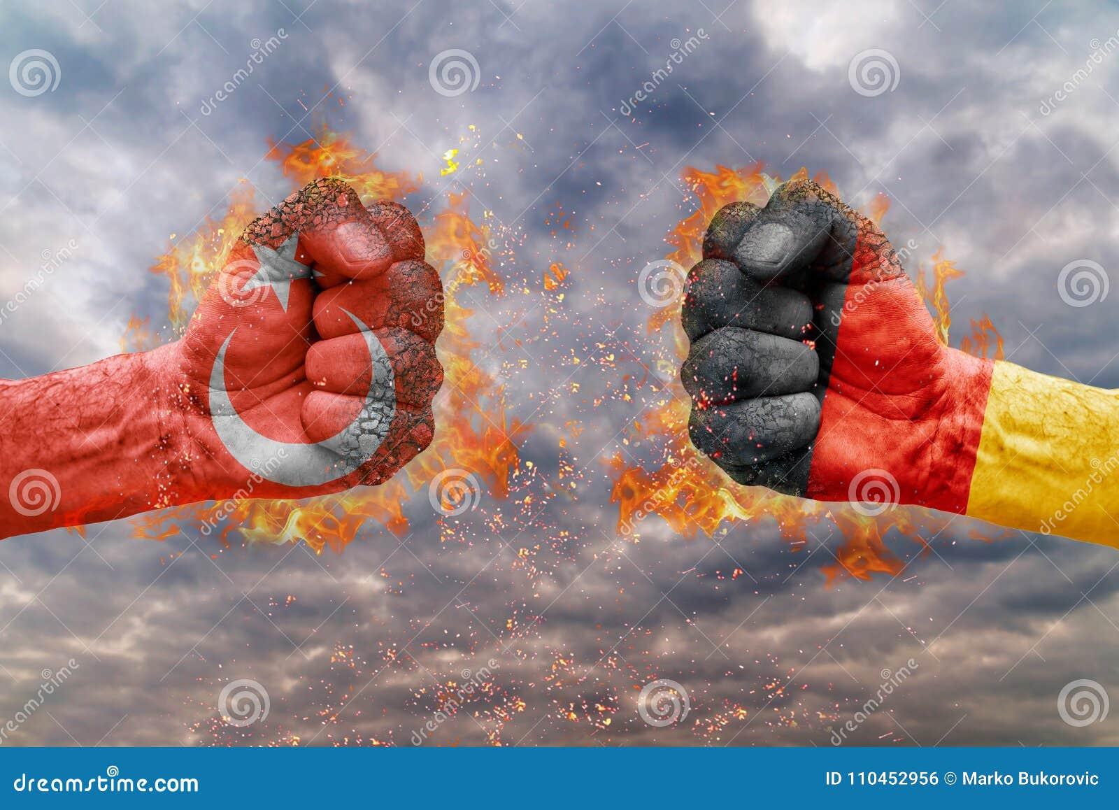 Faust zwei mit der Flagge von der Türkei und von Deutschland gegenübergestellt an einander