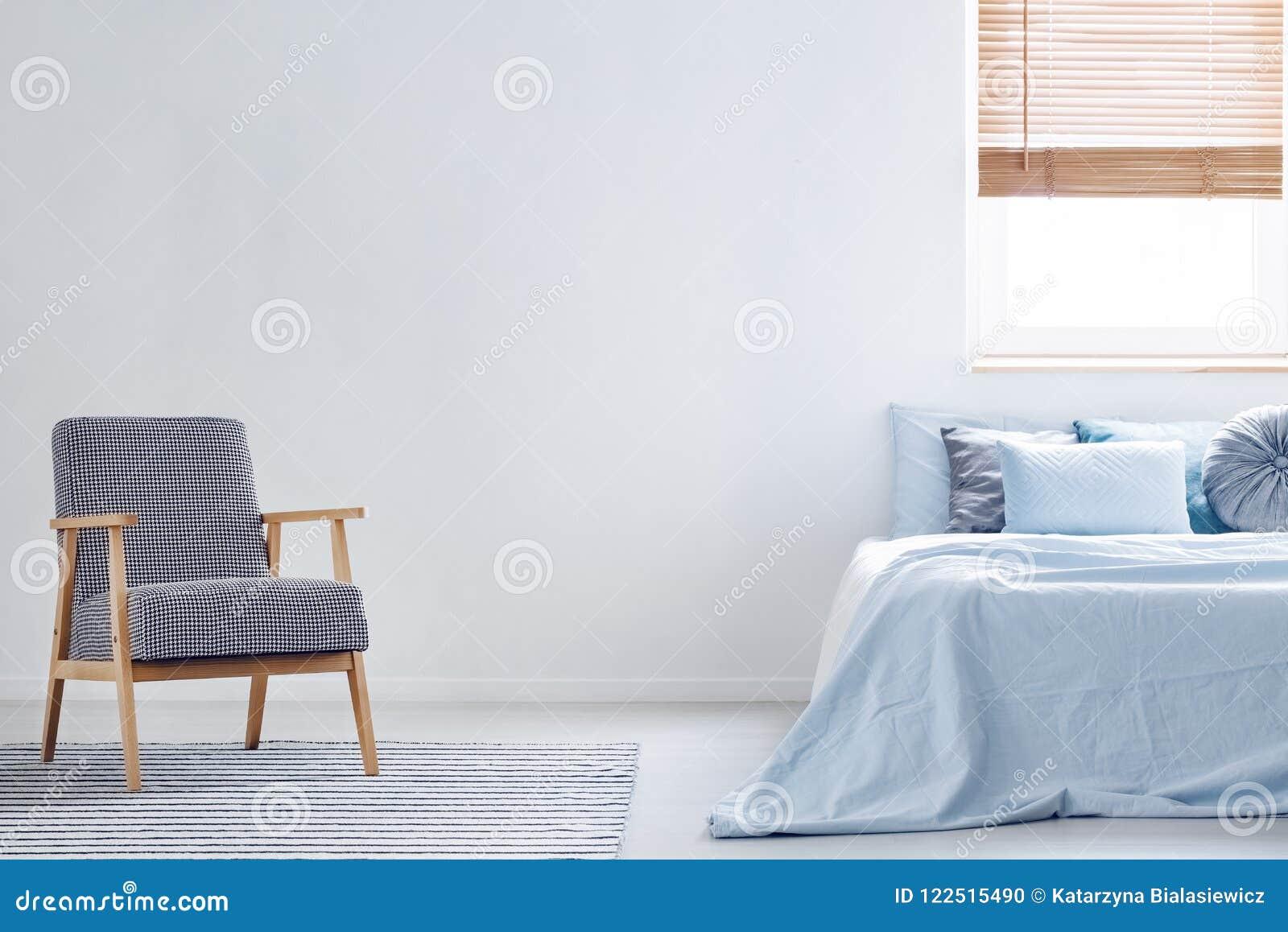 Fauteuil modelé sur le tapis dans l intérieur minimal de chambre à coucher avec le bl