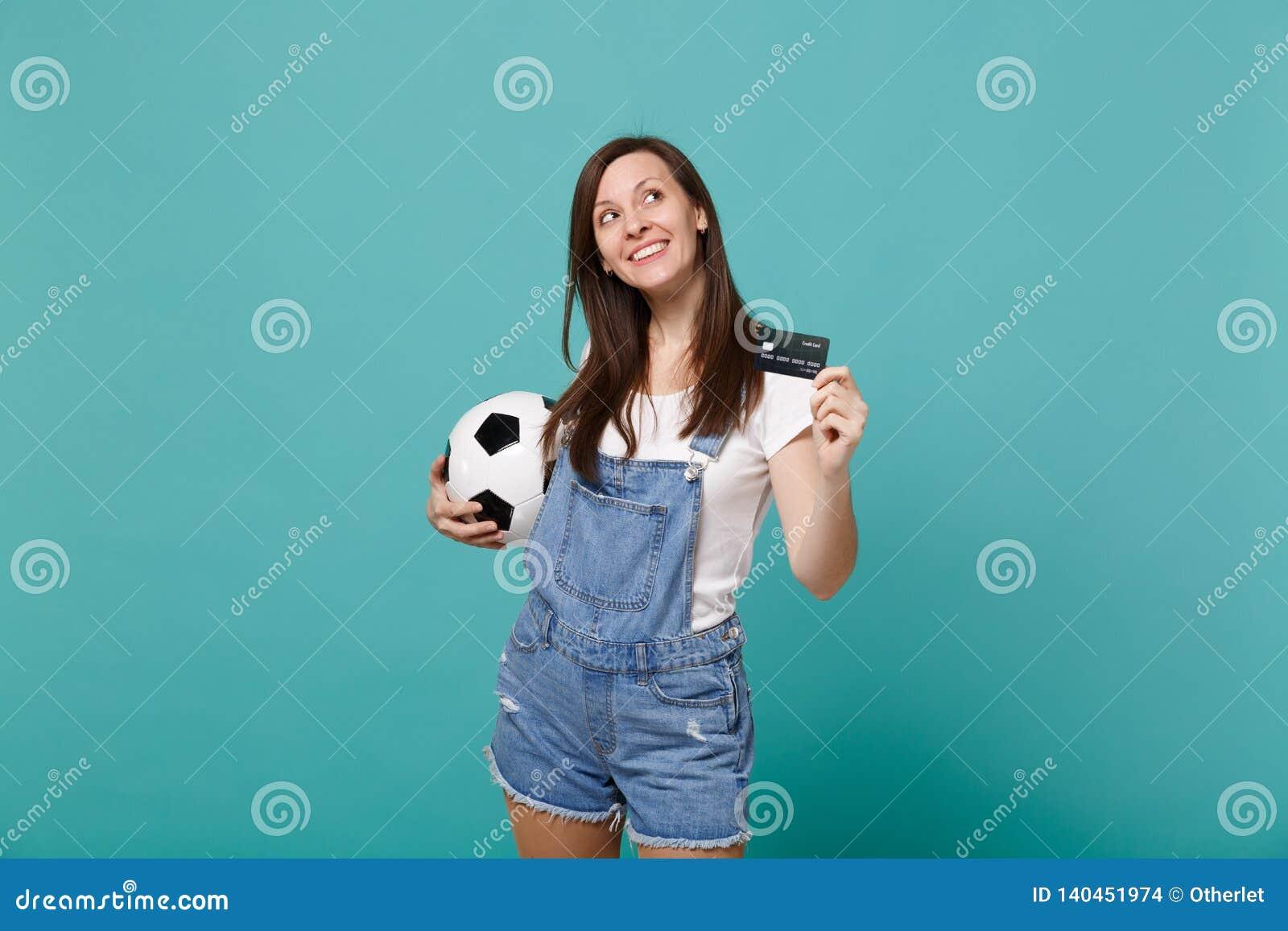 Favorit- lag för eftertänksam fotbollsfanservice för ung kvinna med fotbollbollen, krediteringskontokort som ser upp isolerad på