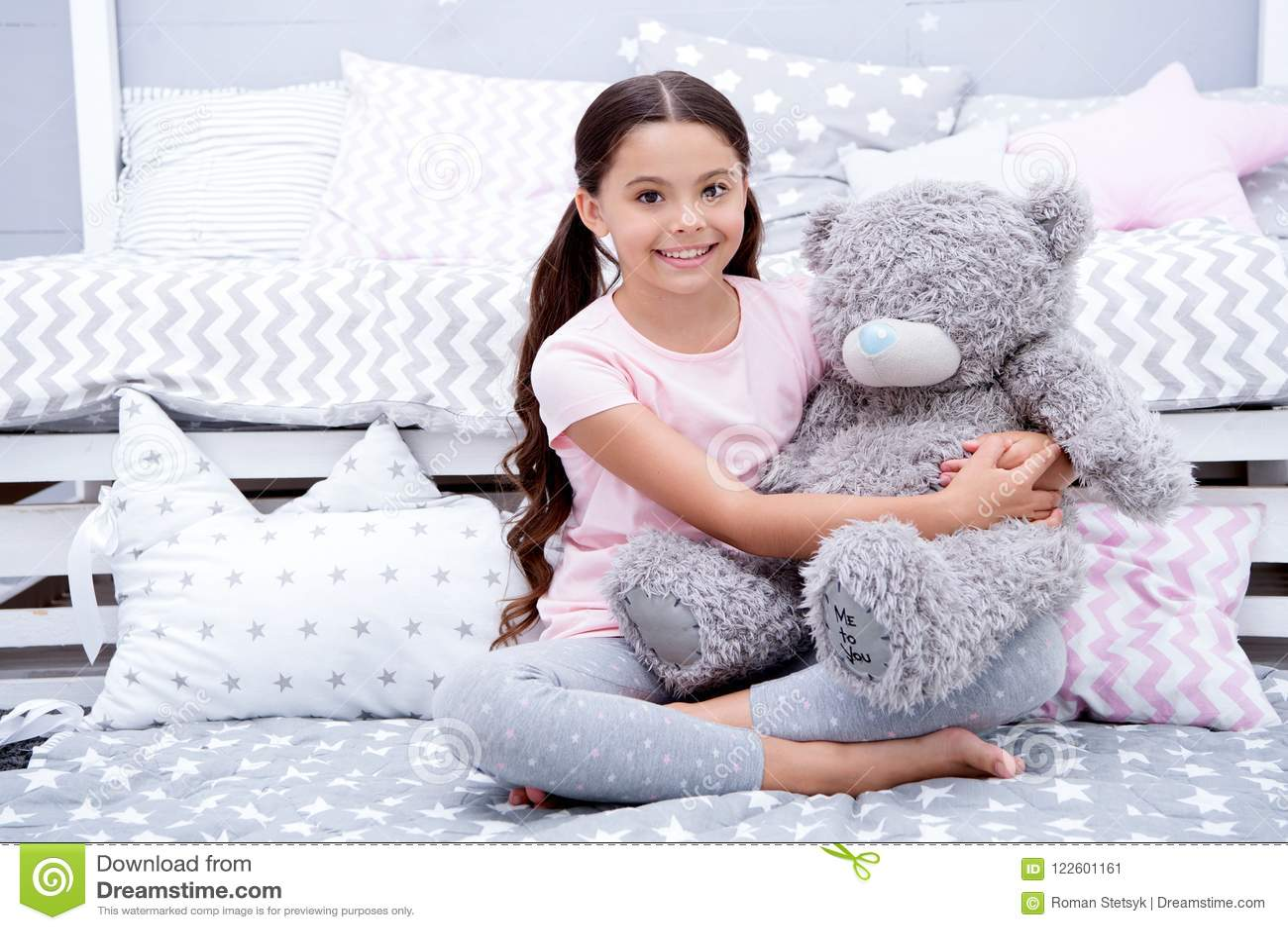Favorit- leksak Flickabarnet sitter på björn för sängkramnalle i hennes sovrum Ungen förbereder sig att gå att bädda ned Angenäm