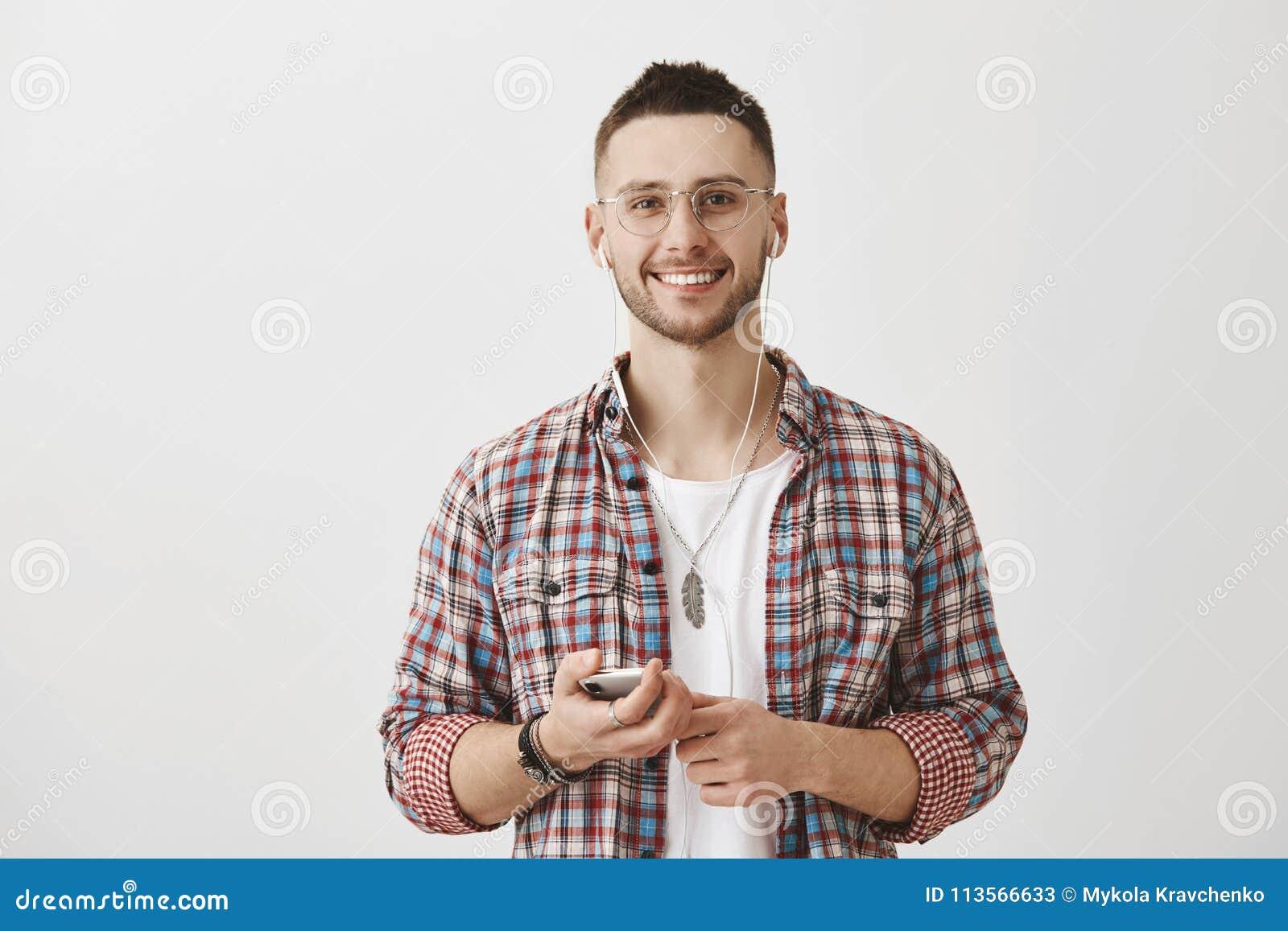 Favorit- musikhjälp som är produktiv under dag Stående av den stiliga lyckliga caucasian grabben i exponeringsglas som rymmer sma
