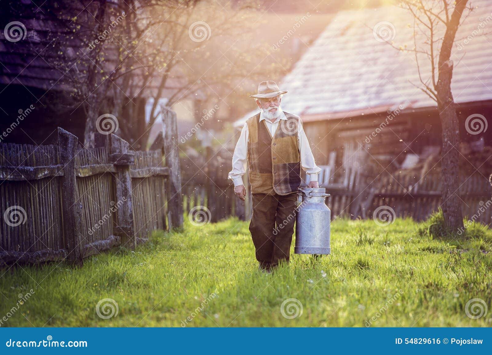 Fazendeiro com chaleira do leite