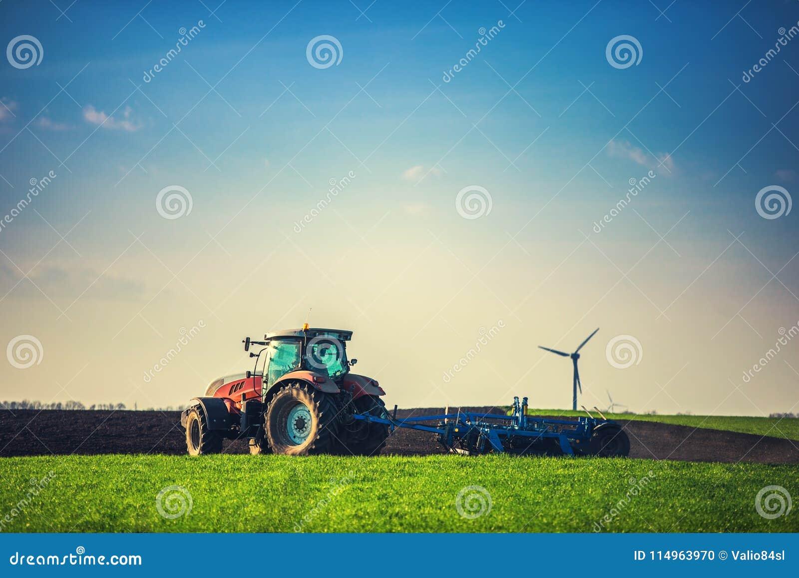 Fazendeiro com o trator que semeia colheitas no campo