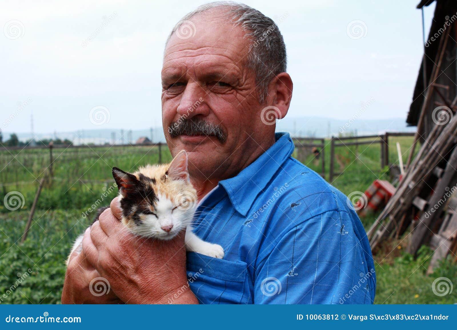 Fazendeiro idoso com um gato colorido