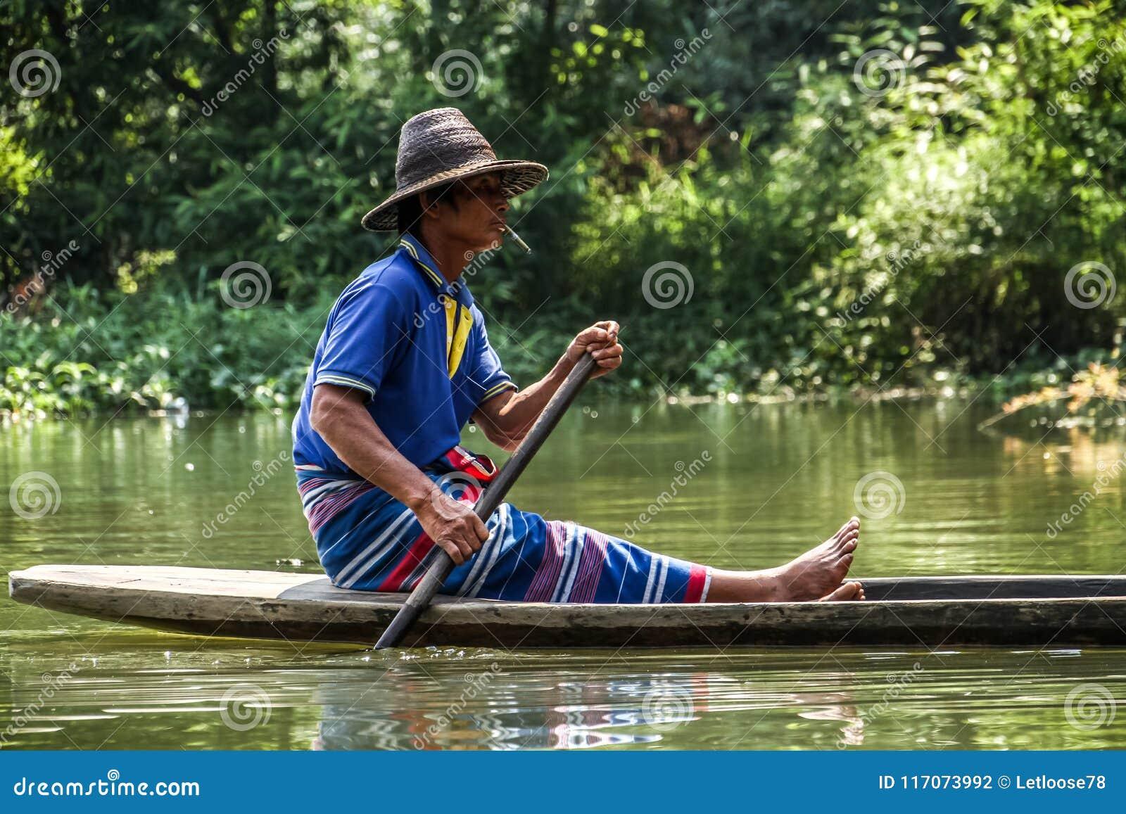 Fazendeiro local que rema seu pirogue tradicional fora da caverna sadan, Hpa-an, distrito de Hpa-an, Myanmar