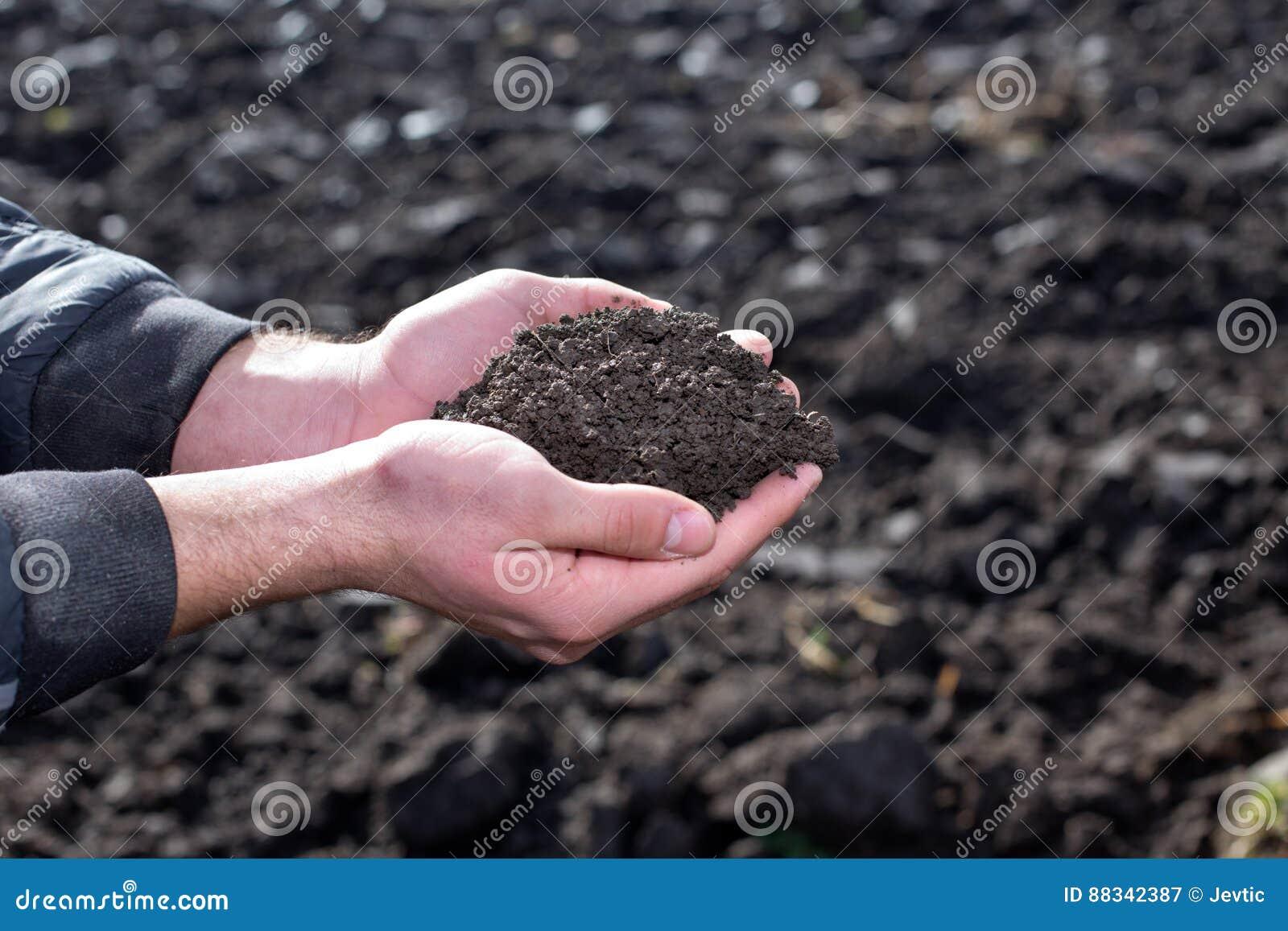 Fazendeiro que guarda o solo nas mãos no campo