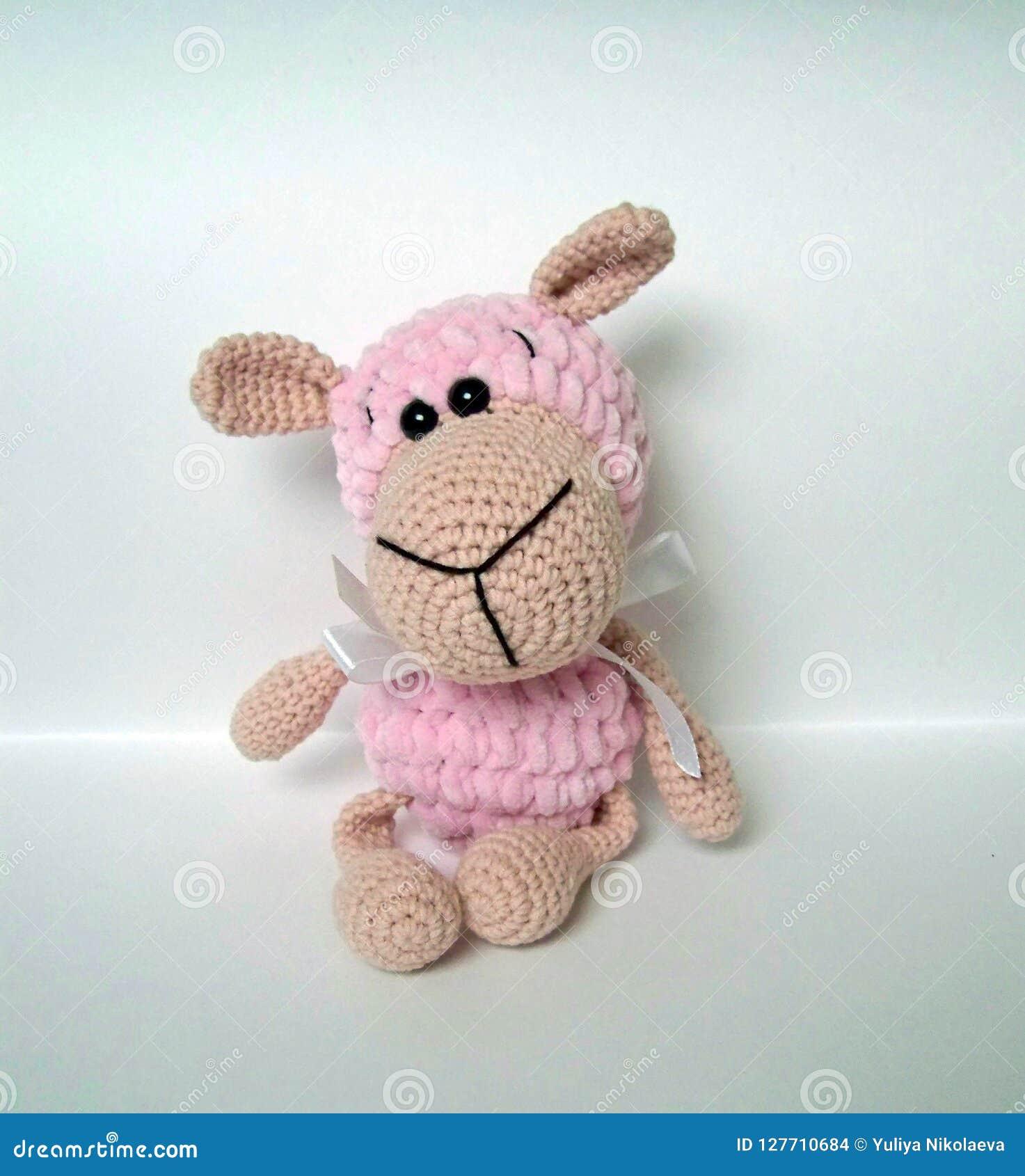 Fazer crochê a boneca Um feito a mão faz crochê a boneca de um cordeiro pequeno no rosa