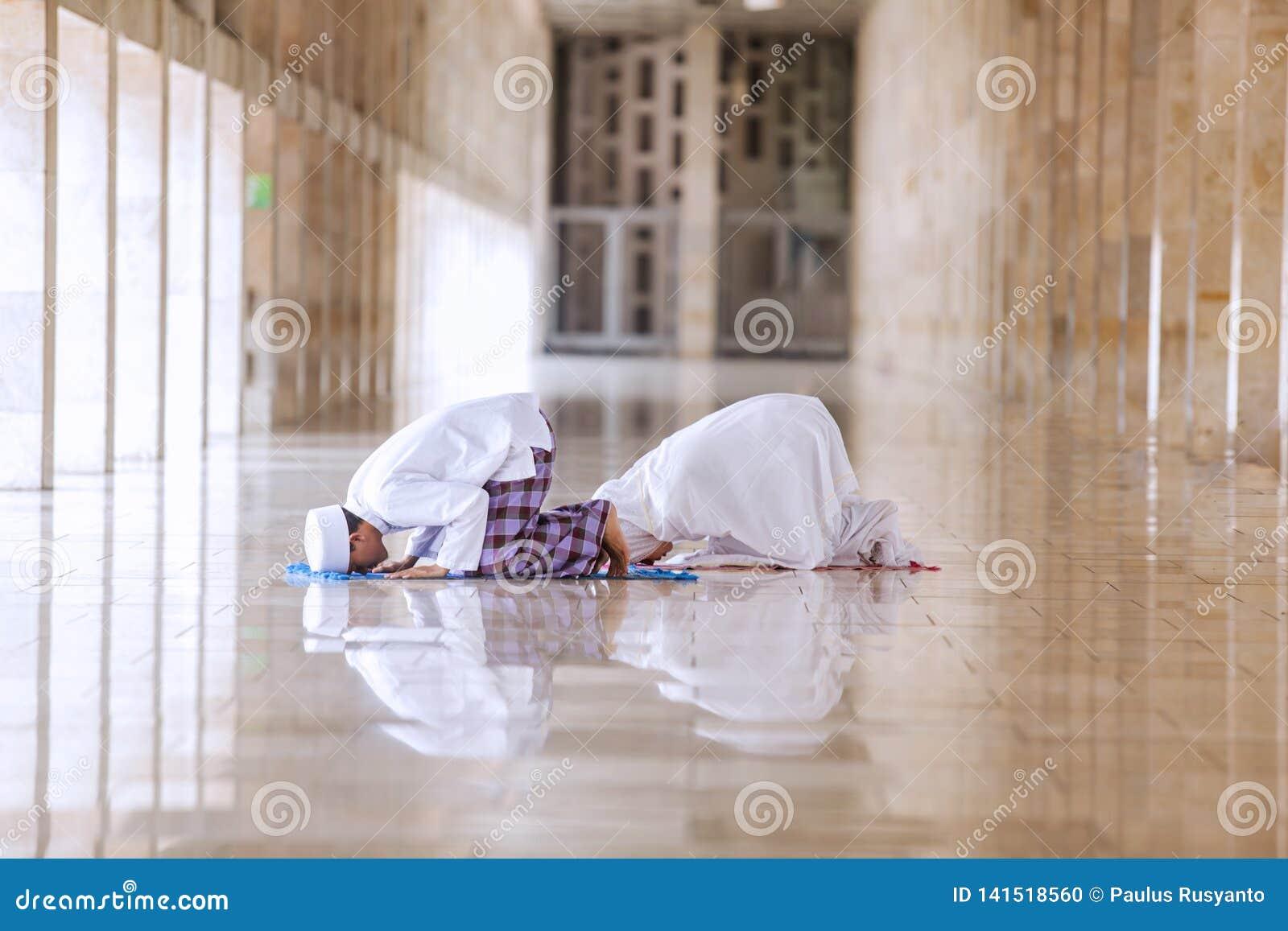 Fazer religioso dos pares reza na mesquita