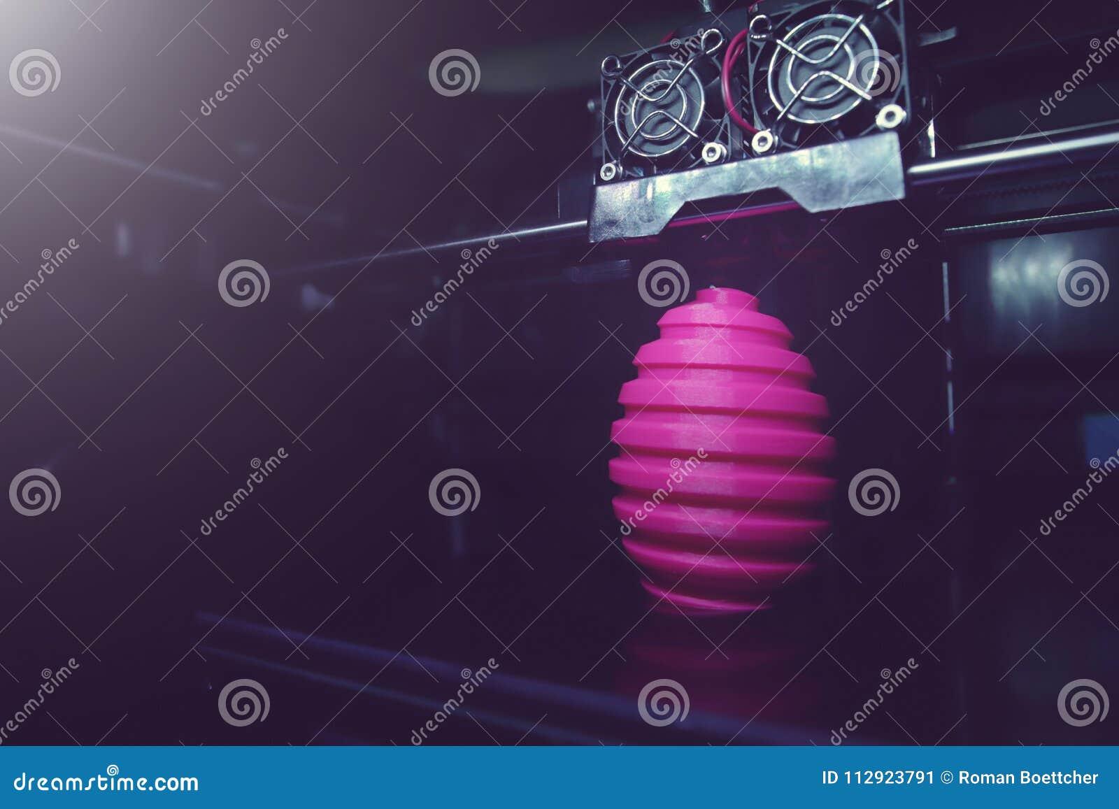 FDM 3D打印机制造业使桃红色复活节彩蛋雕塑-在对象、打印头和机器房间的广角看法受伤