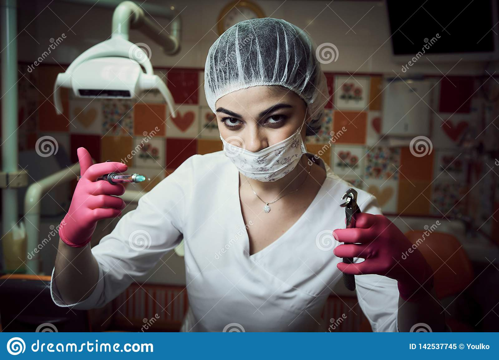 The fear of dental treatment. Children`s dentist girl at the dentist office keeps the instrument and scares