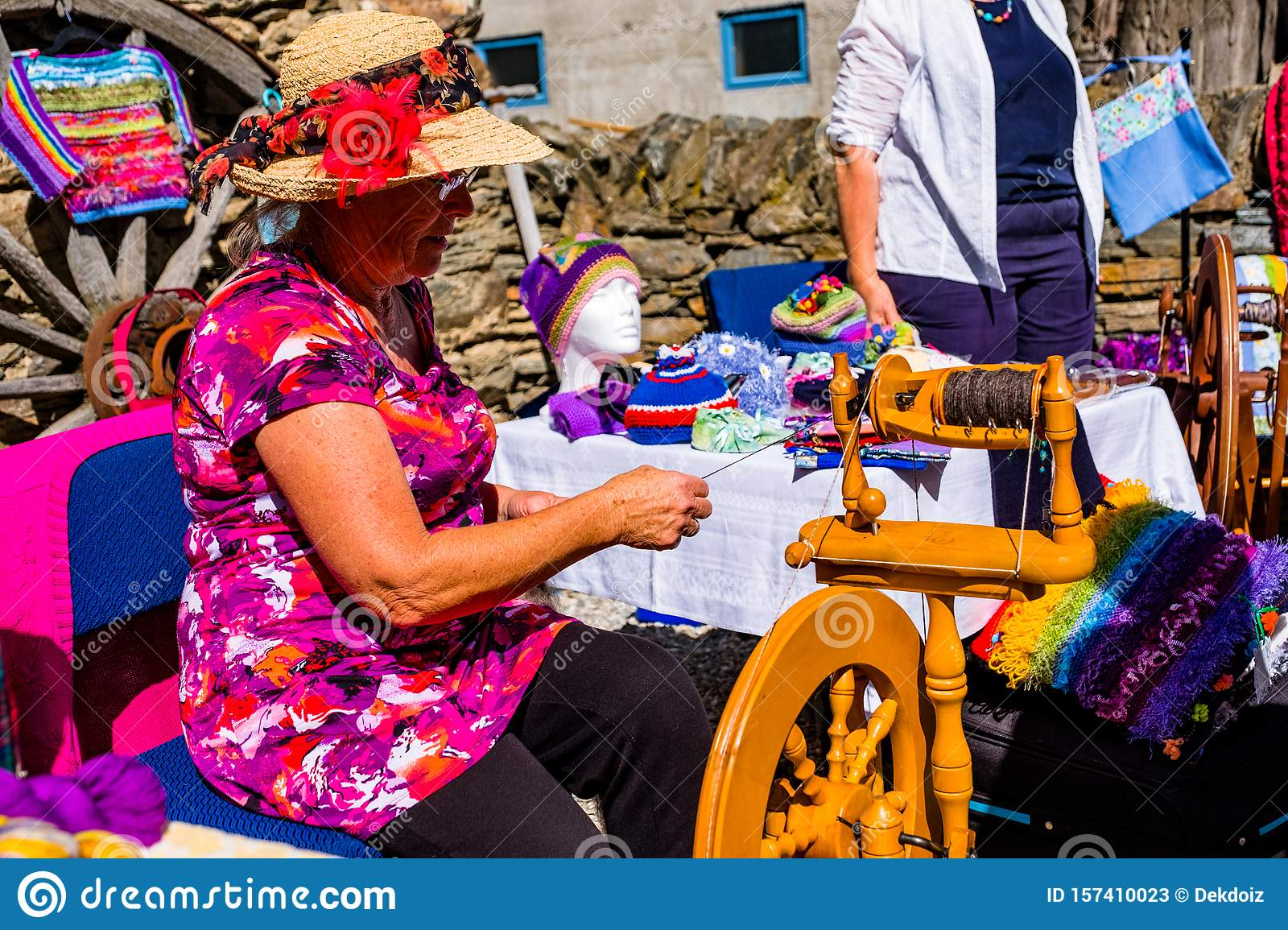 2019 FEB 12, New Zealand, Cromwell, A lady using the old traditional wooden yarn machine in market