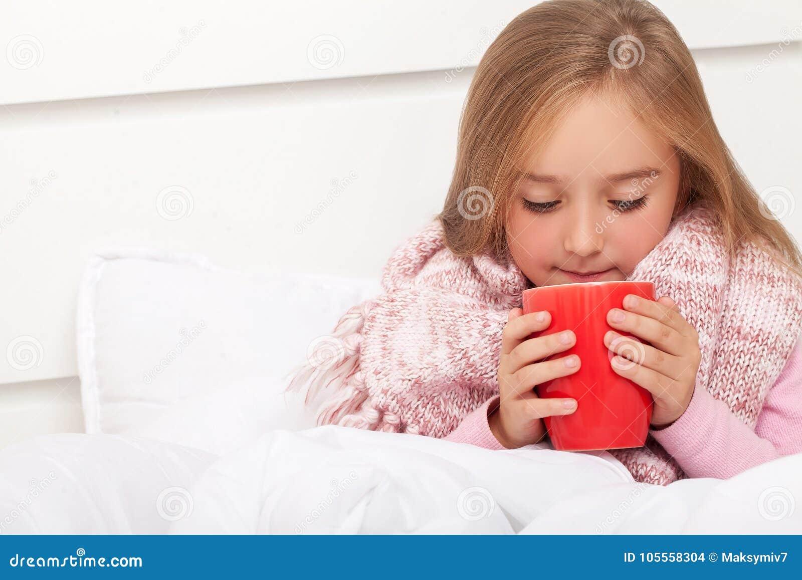 Feber, förkylning och influensa - mediciner och varmt te i nära, sjuk flicka I