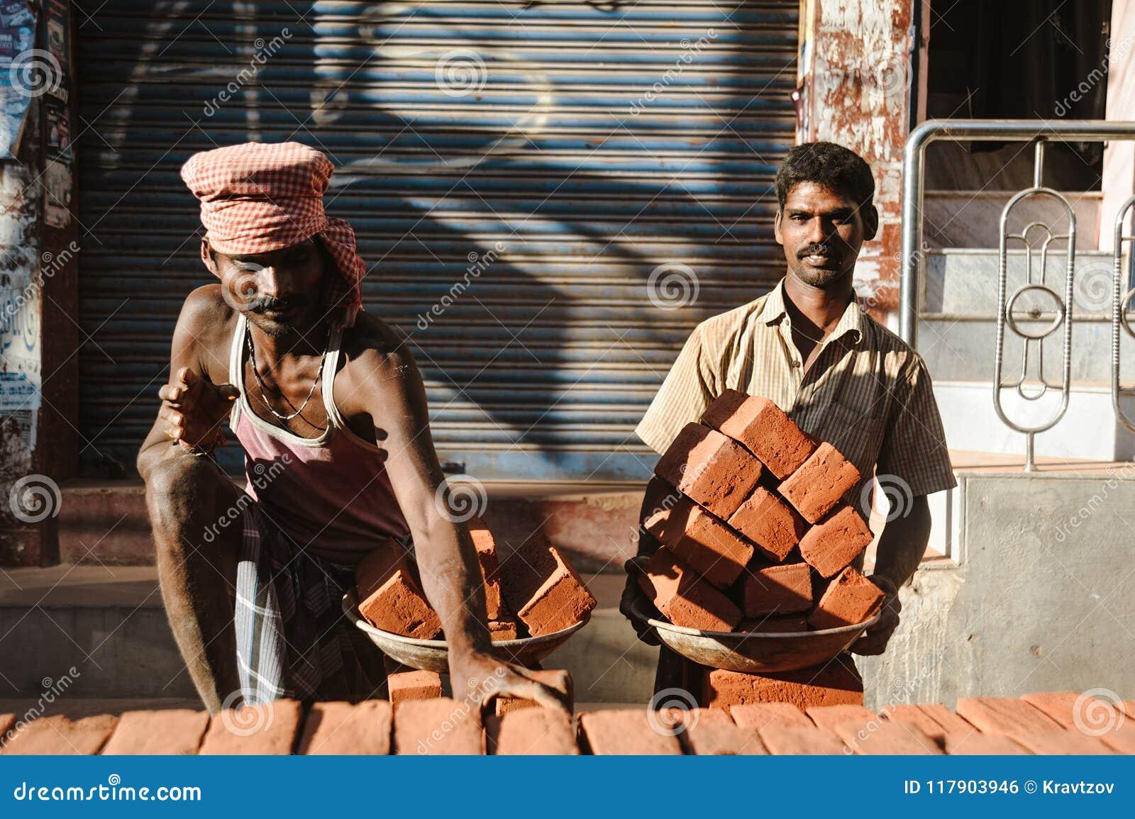23. Februar 2018 Madurai, Indien, zwei indische Arbeitskräfte herein draußen mit Platten ful von Ziegelsteinen