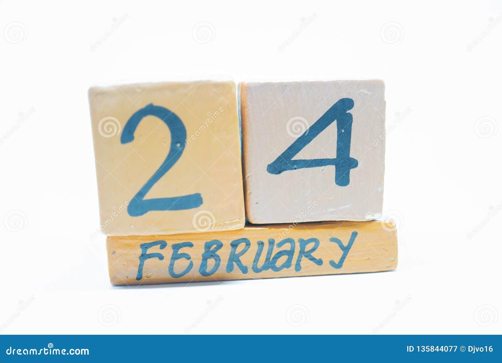24 februari Dag 24 van maand, met de hand gemaakte houten die kalender op witte achtergrond wordt geïsoleerd Wintermaand, dag van