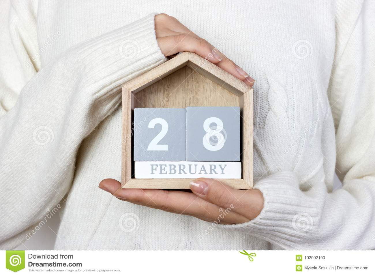 February 28 in the calendar. the girl is holding a wooden calendar. Rare Disease Day, Shrove Tuesday, International Pancake Day