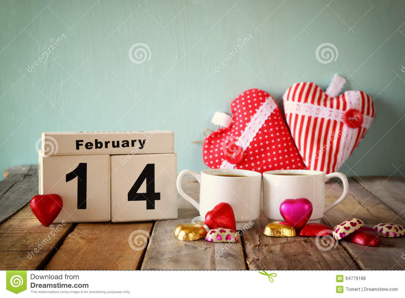 February 14th wooden vintage calendar with colorful heart shape chocolates next to couple cups on wooden table. selective focus