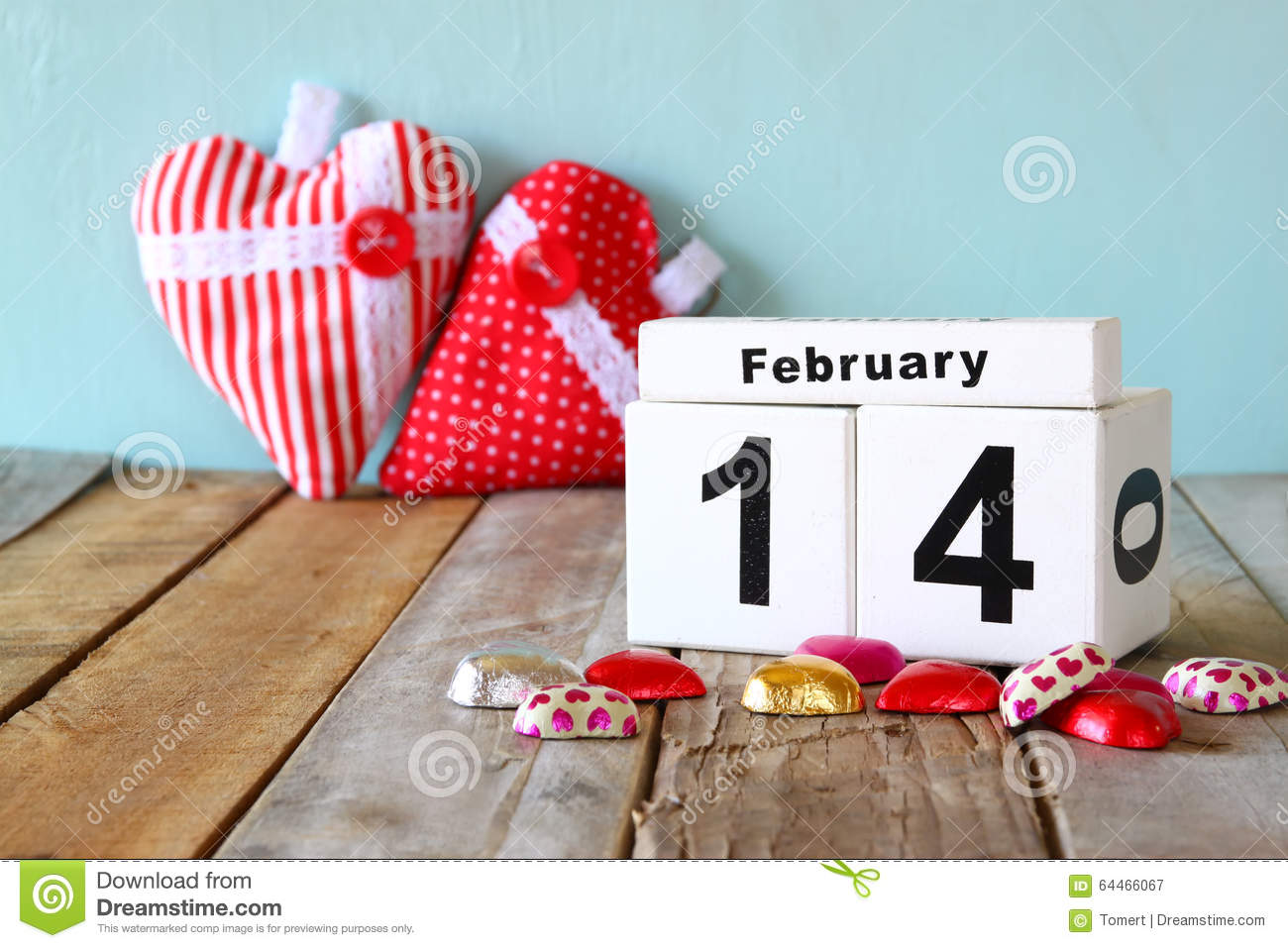 February 14th wooden vintage calendar with colorful heart shape chocolates on wooden table. selective focus.