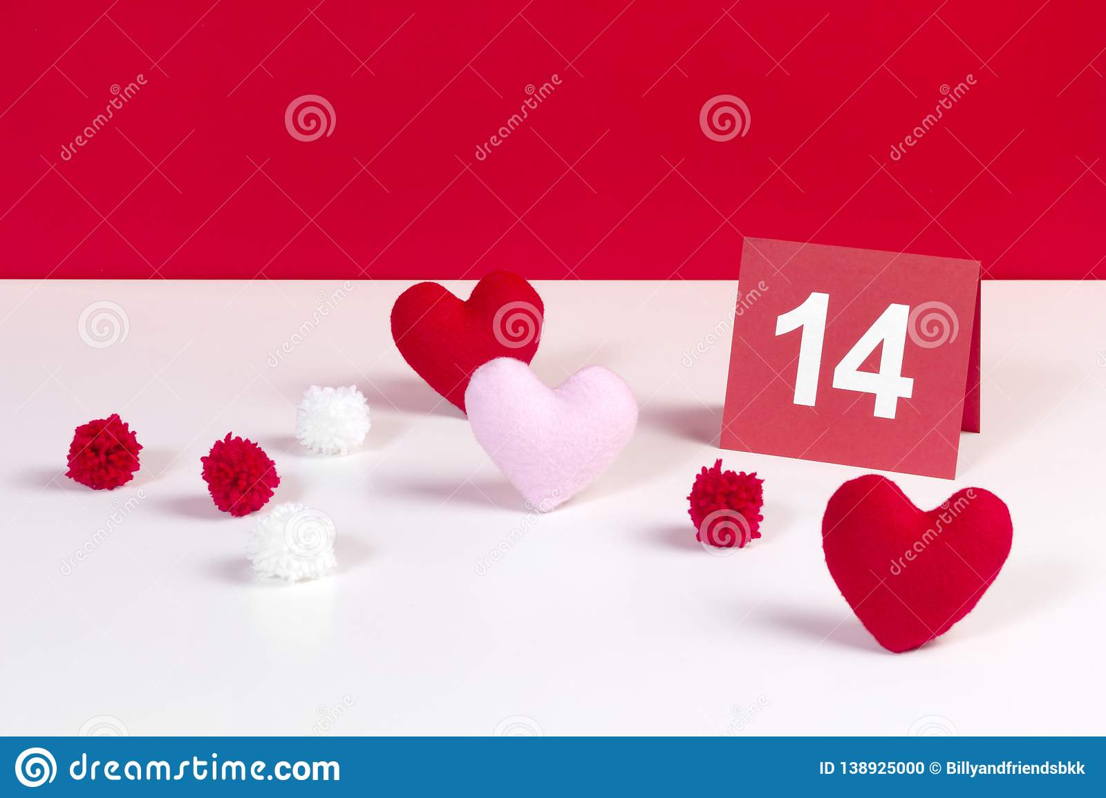 14 February Valentine`s Day red card concept decorated with heart shaped fabrics and pom pom on red and white background