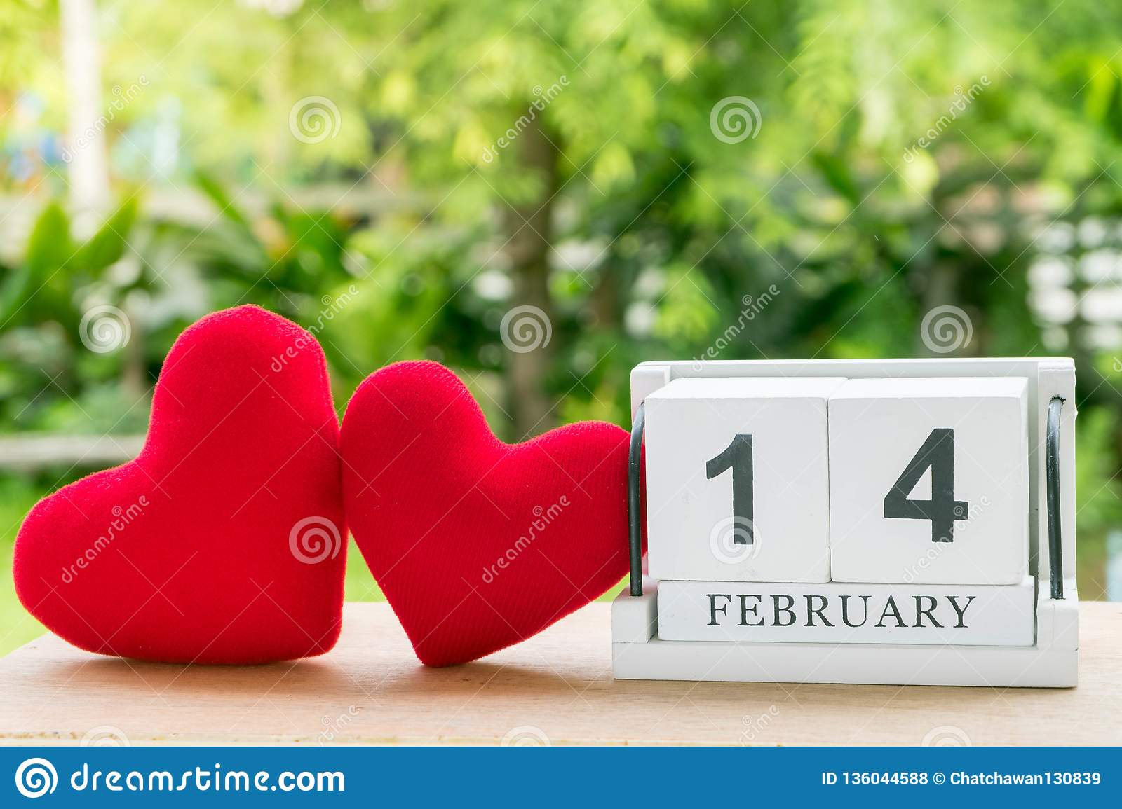 The February 14 wooden calendar features two red hearts placed side by side with a natural background.Valentine day