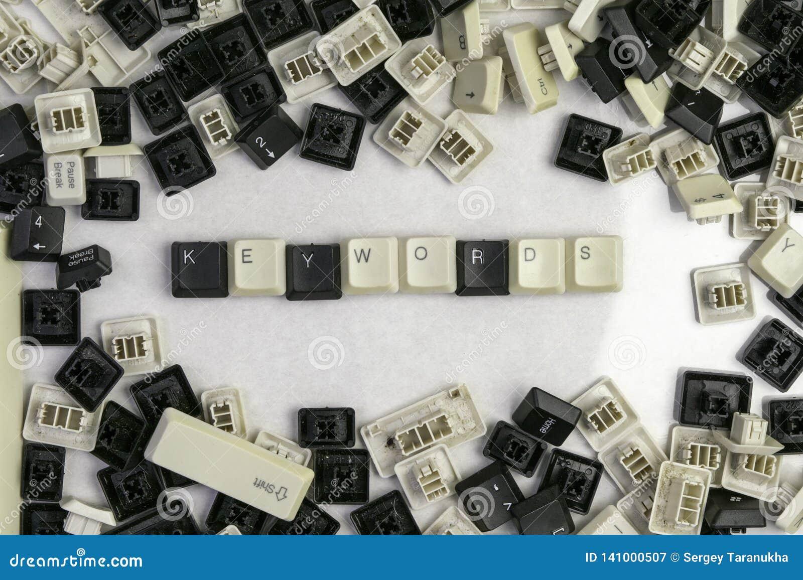 Fechando trabalhos em microstocks, as palavras-chaves da palavra dobradas das chaves do teclado velho