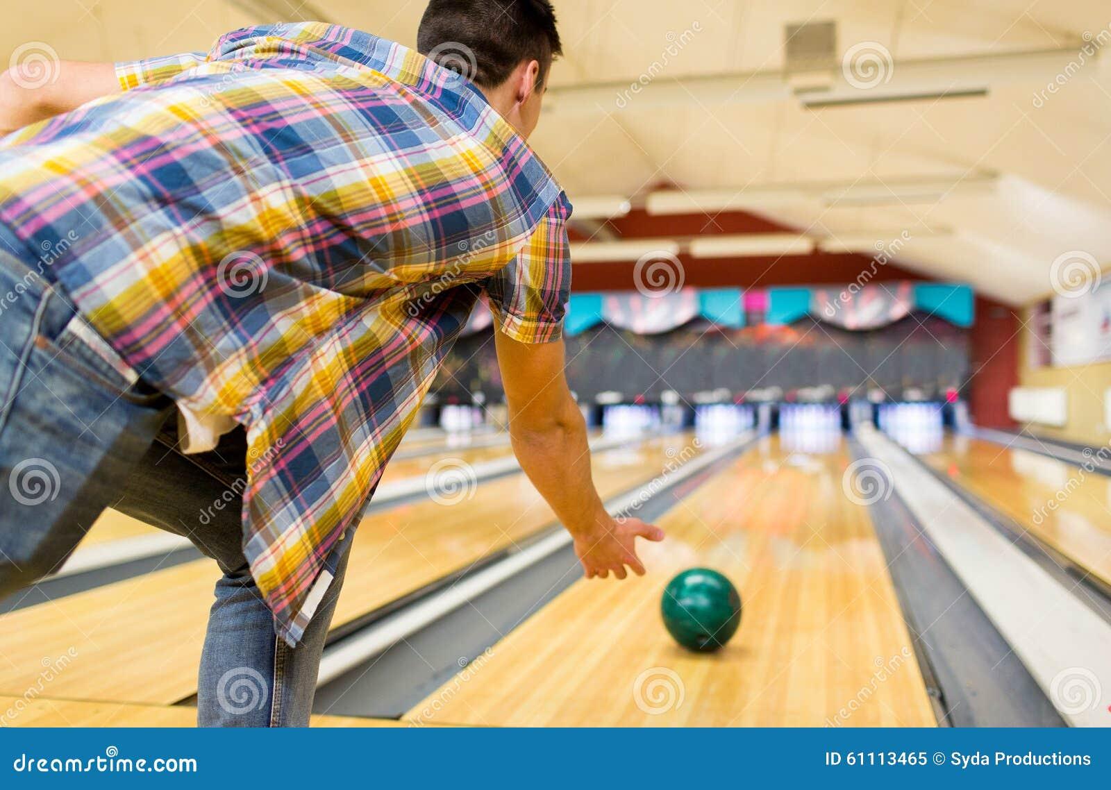 Feche acima da bola de jogo do homem no clube do boliches