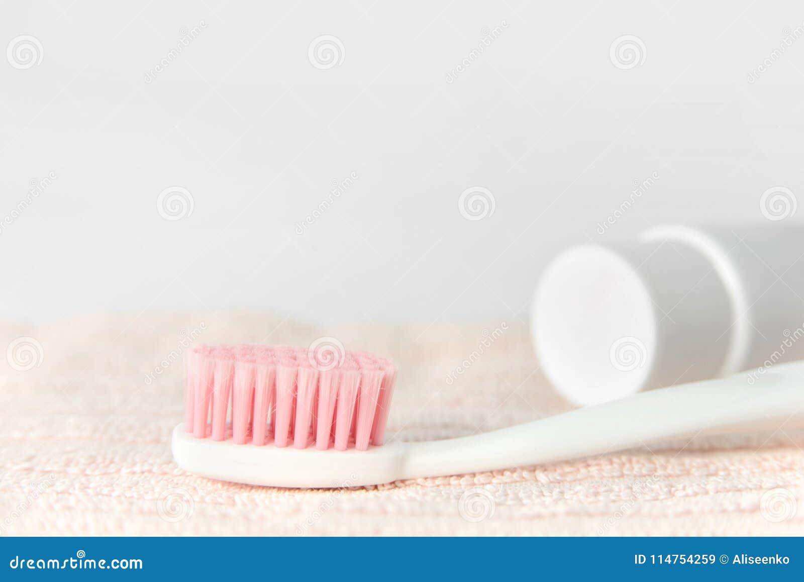 Feche acima da escova de dentes branca plástica com cerda cor-de-rosa e do dentífrico no tubo na toalha cor-de-rosa