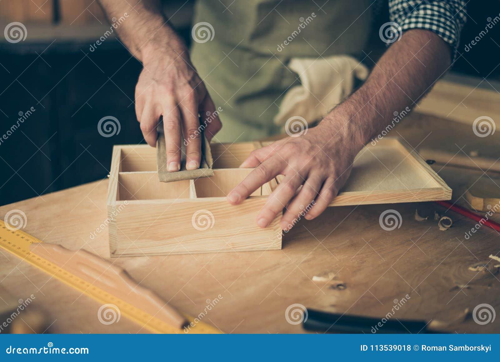 Feche acima da foto colhida das mãos do ` s do handicraftsman que lixam o sur