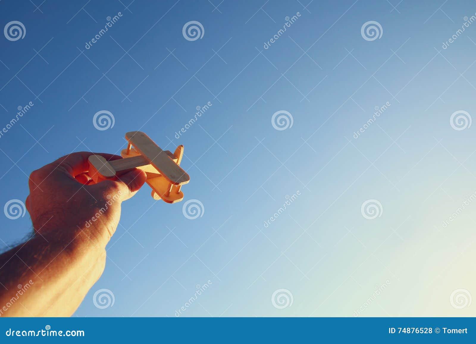Feche acima da foto da mão do homem que guarda o avião de madeira do brinquedo