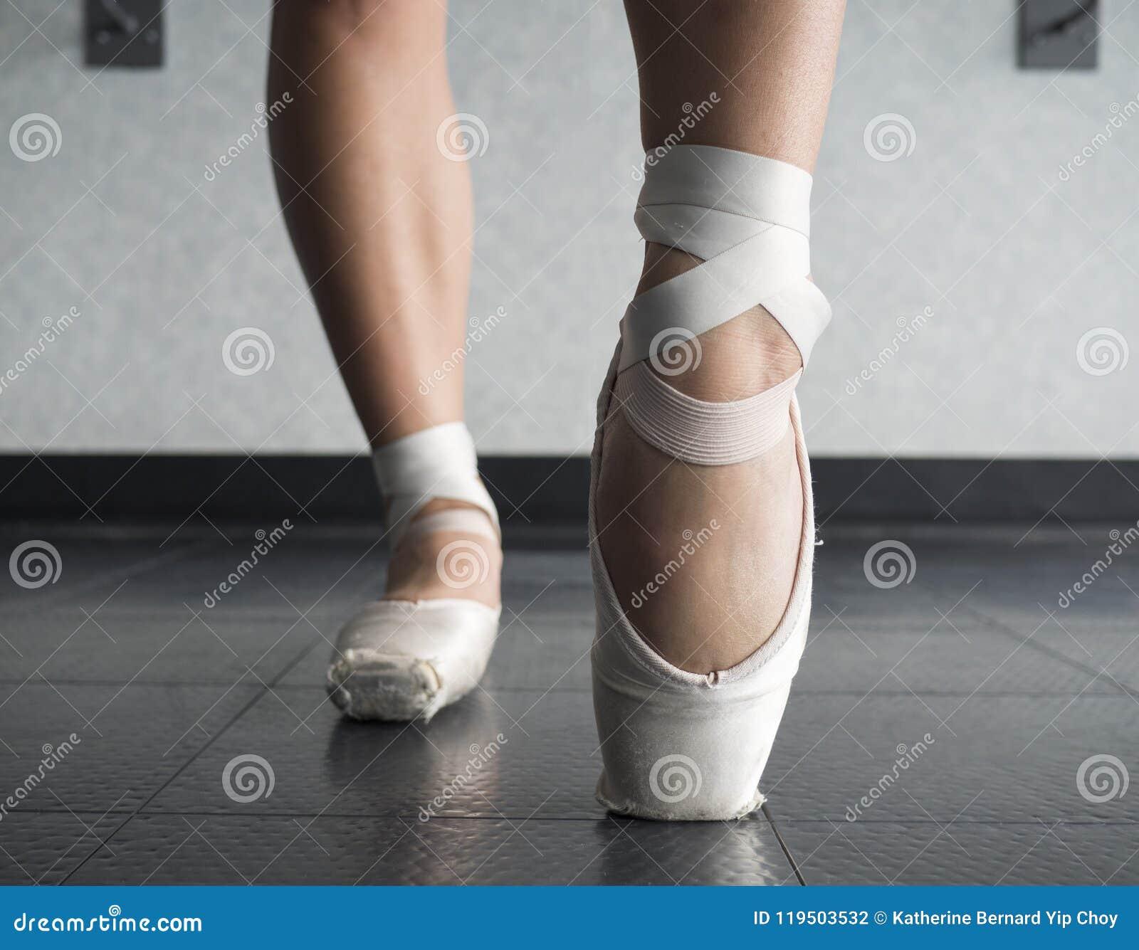 Feche acima da ideia de uma dança do bailado da bailarina, aquecendo seus pés na classe do bailado