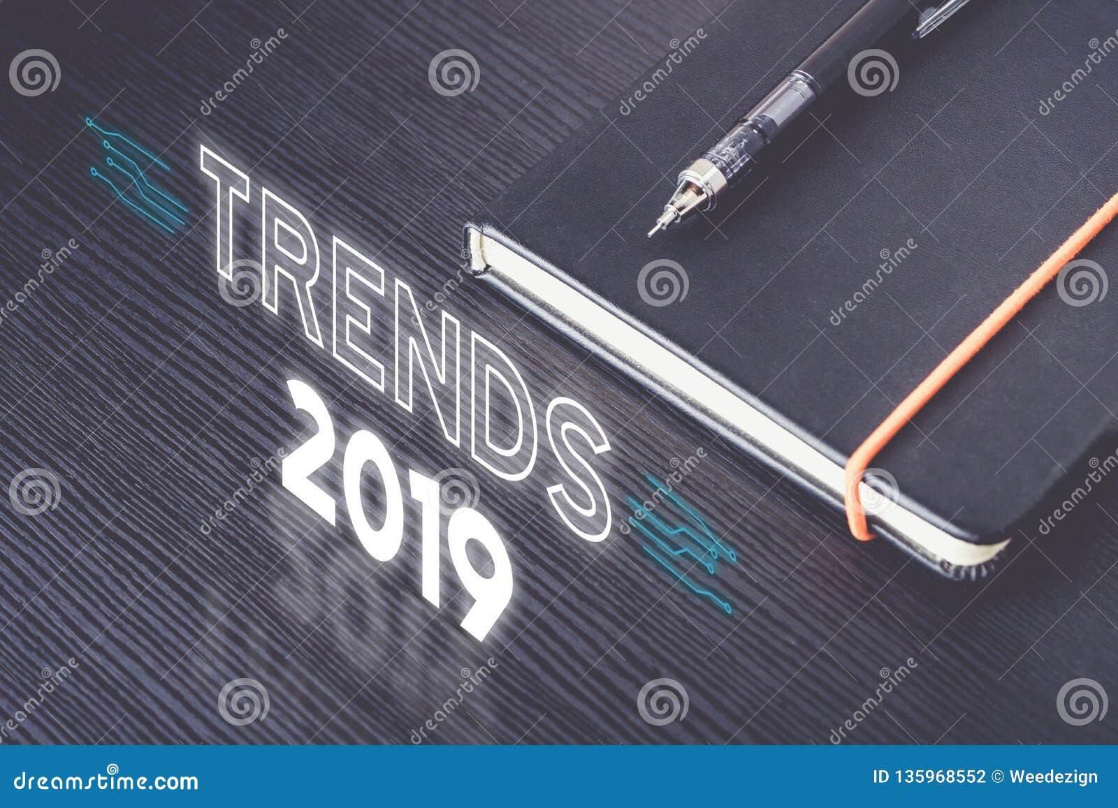 Feche acima da ideia superior das tendências 2019 com o caderno preto com o lápis mecânico moderno na tabela de madeira coisa nov