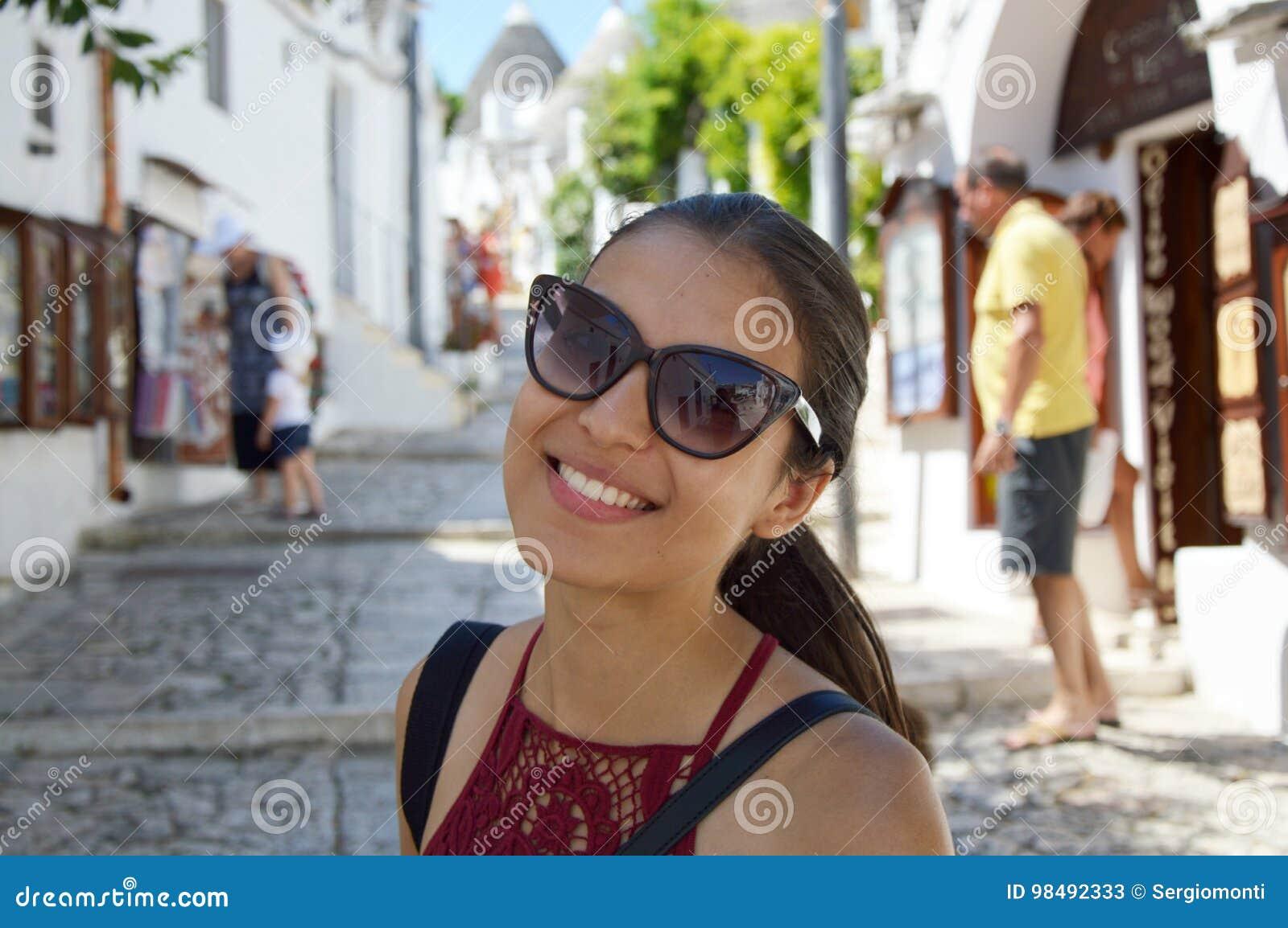 Feche acima da jovem mulher à moda com óculos de sol que sorri no fundo  italiano d0111a54e3