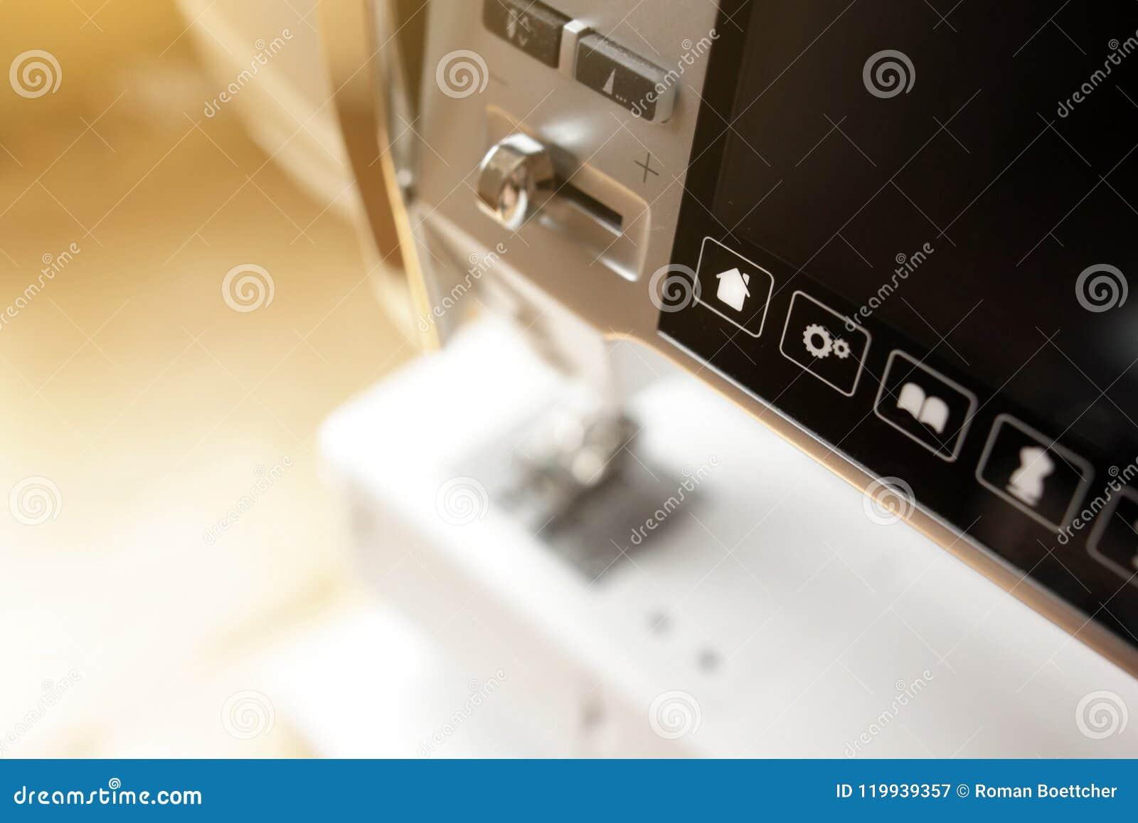 Feche acima da máquina de costura automatizada moderna na luz ensolarada brilhante - controle botões e écran sensível