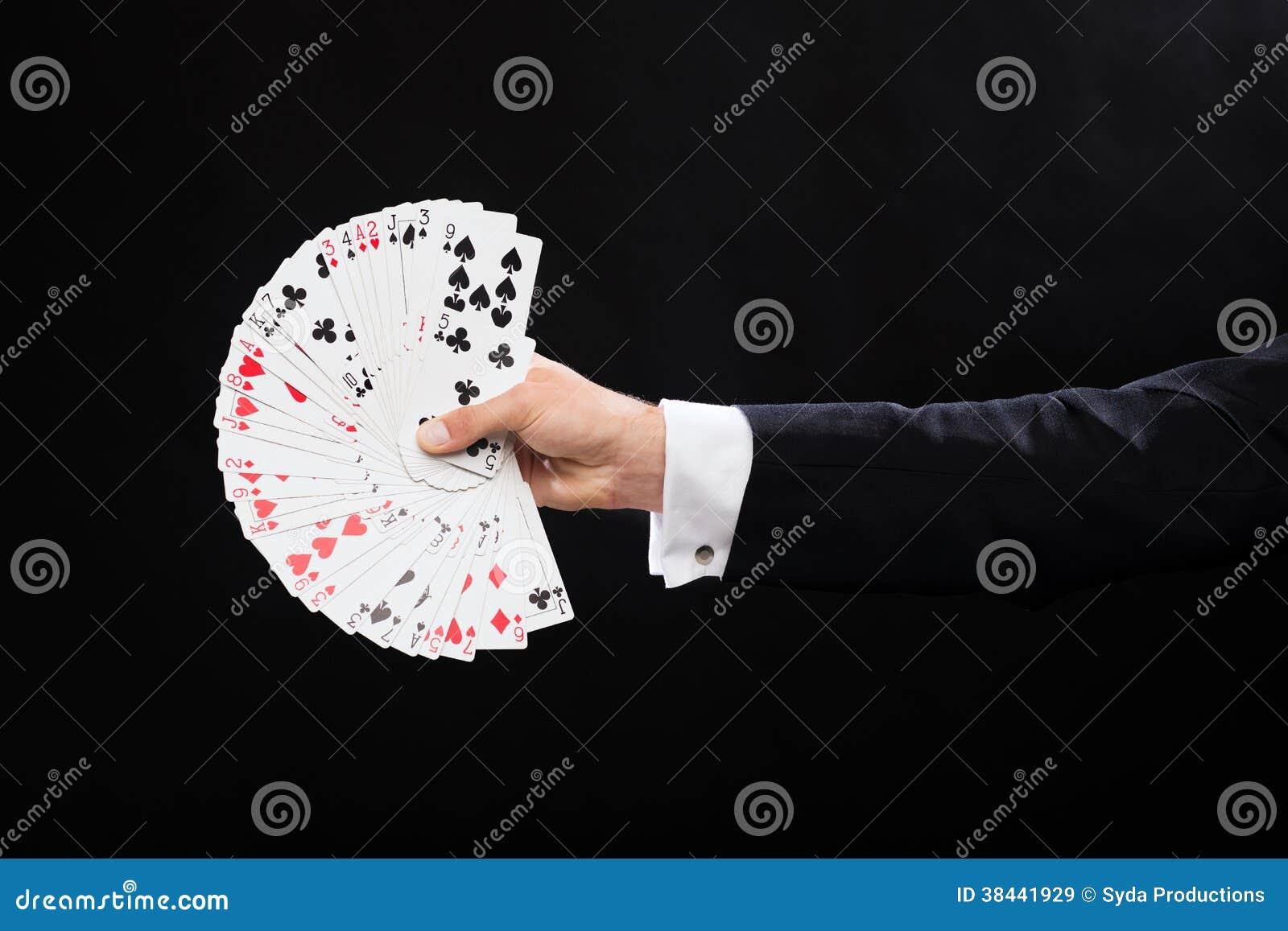 Feche acima da mão do mágico que guarda cartões de jogo