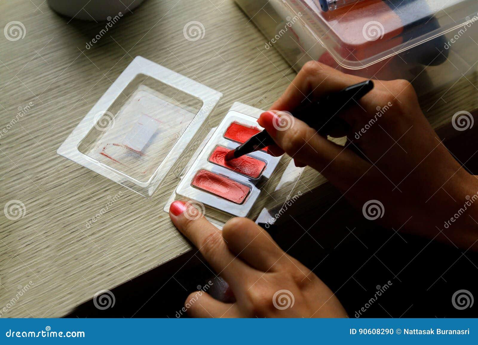 Feche acima da mão do ` s da mulher que aplica a composição com cosmético