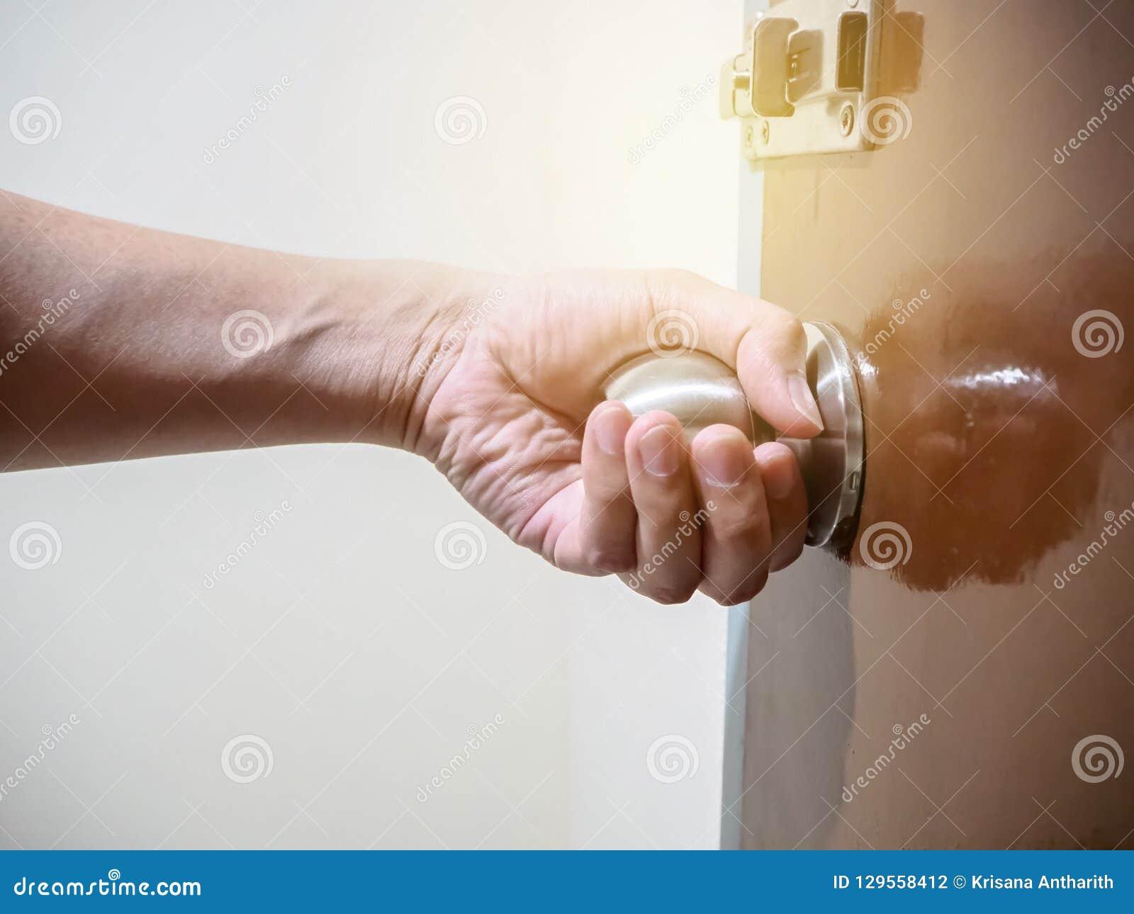 Feche acima da mão que guarda um botão de porta, abrindo ou fechando o doo