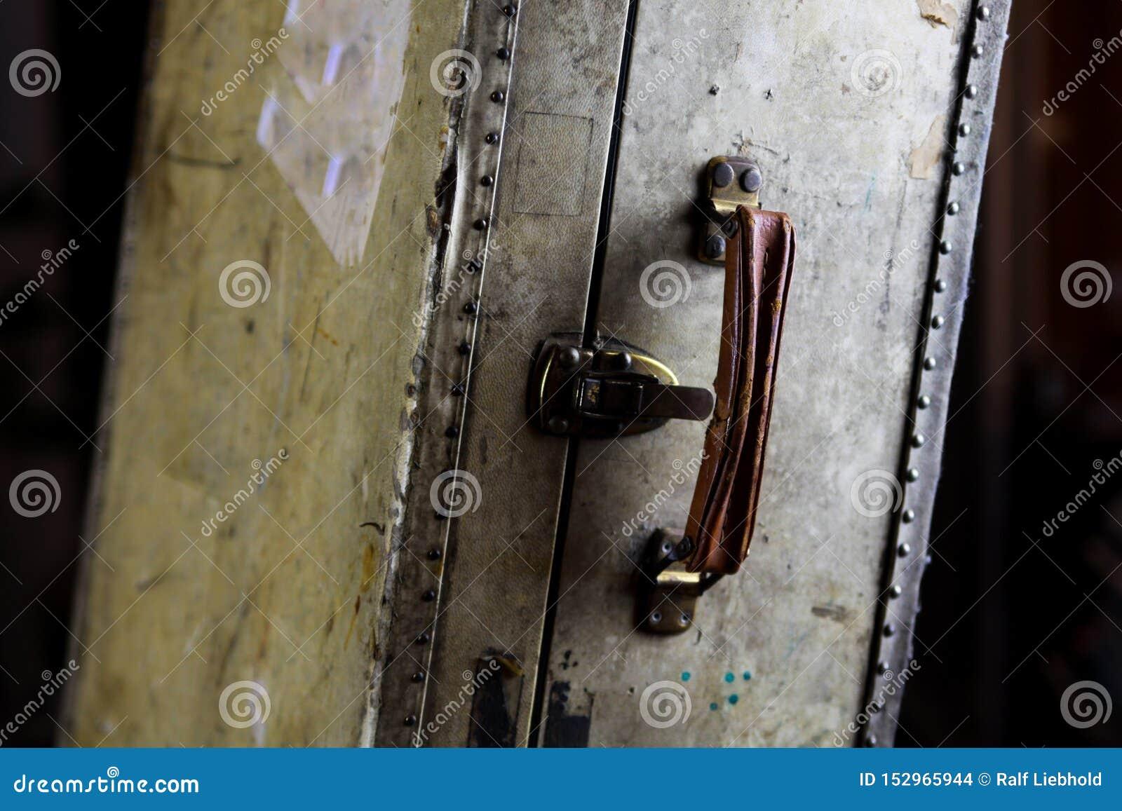 Feche acima da mala de viagem usada velha isolada com rebites, o aperto de couro e os fechamentos de combinação